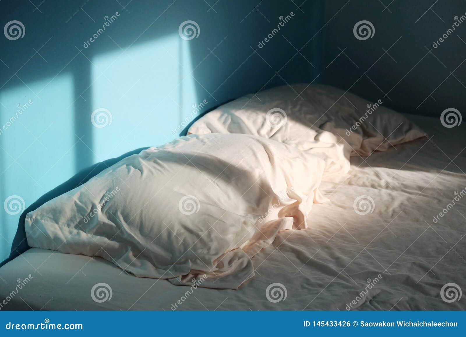 一个对有一个床单的起皱纹的枕头在蓝色室和早晨光