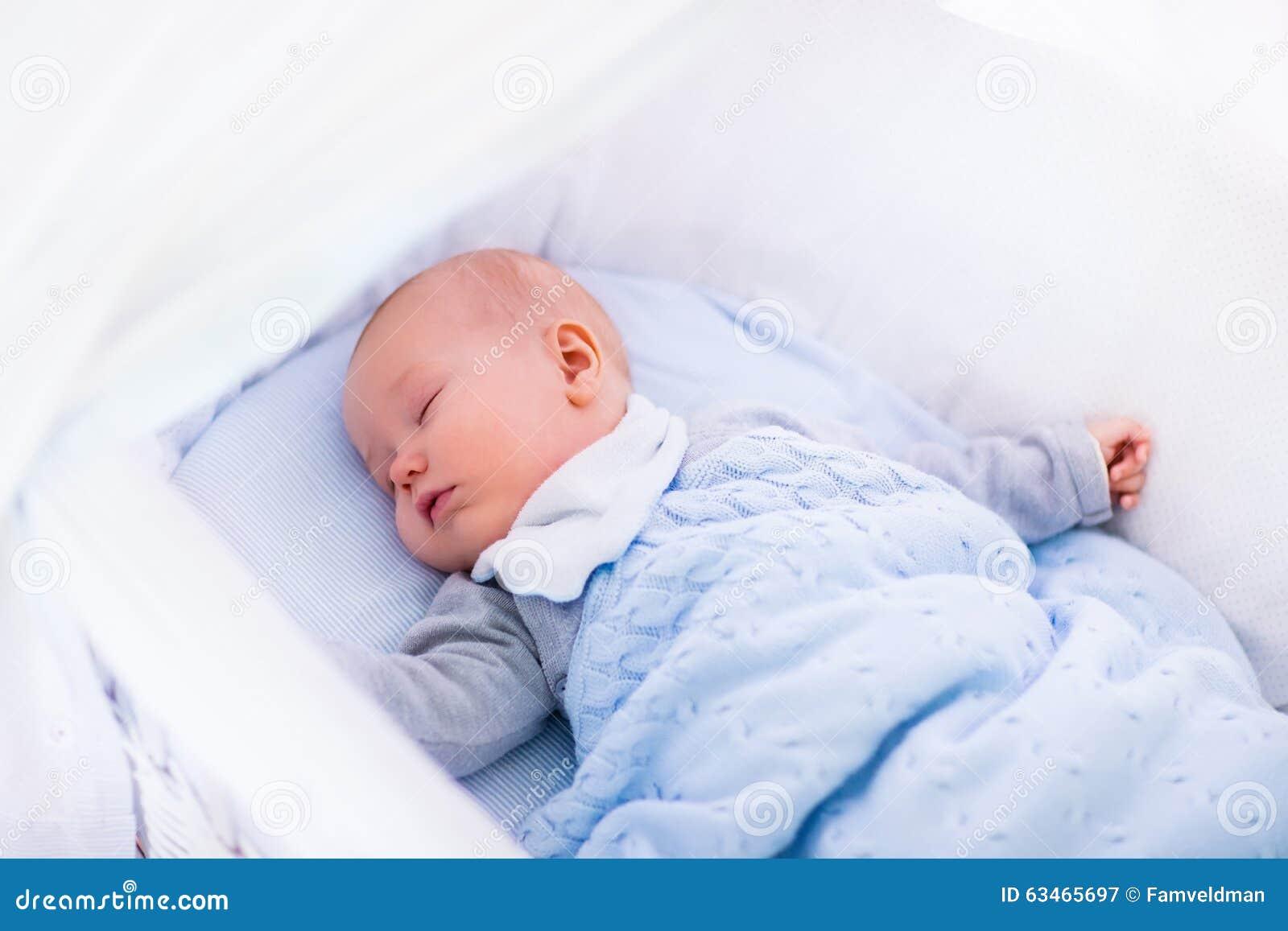 一个小儿床的男婴在被编织的毯子下