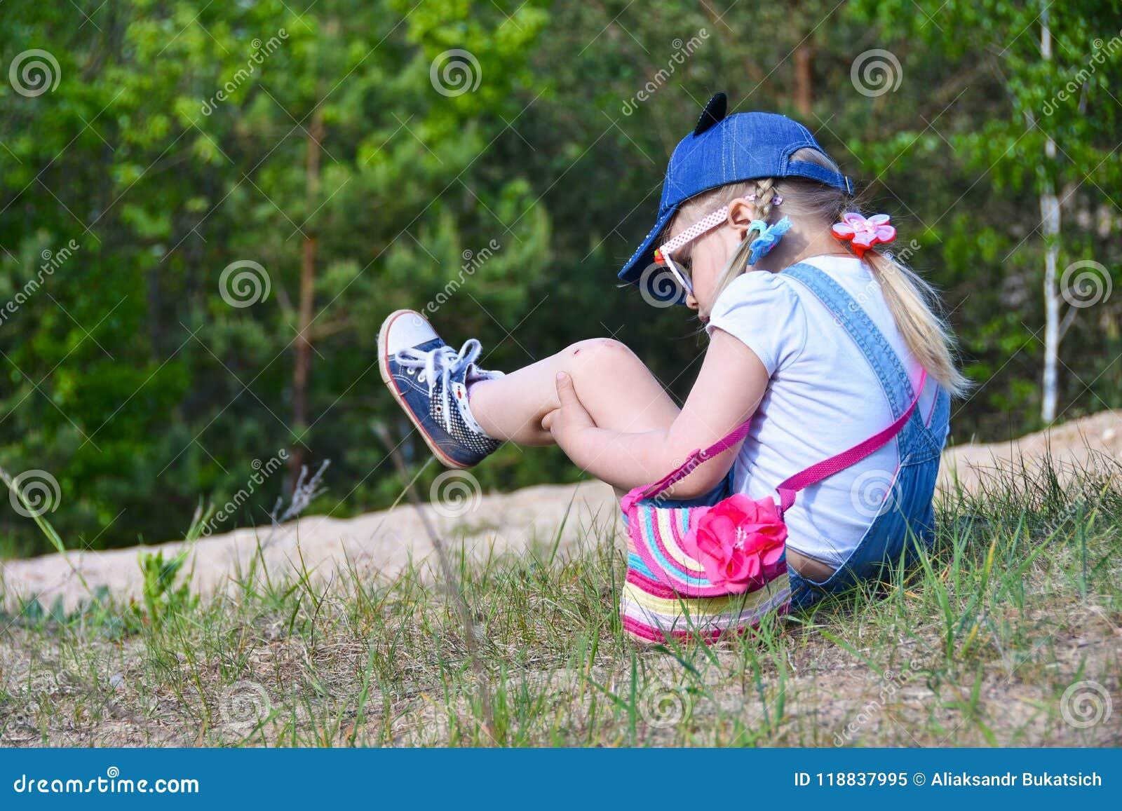 一个小女孩在领域的街道上跌倒了,抓了她的膝盖并且握她的腿