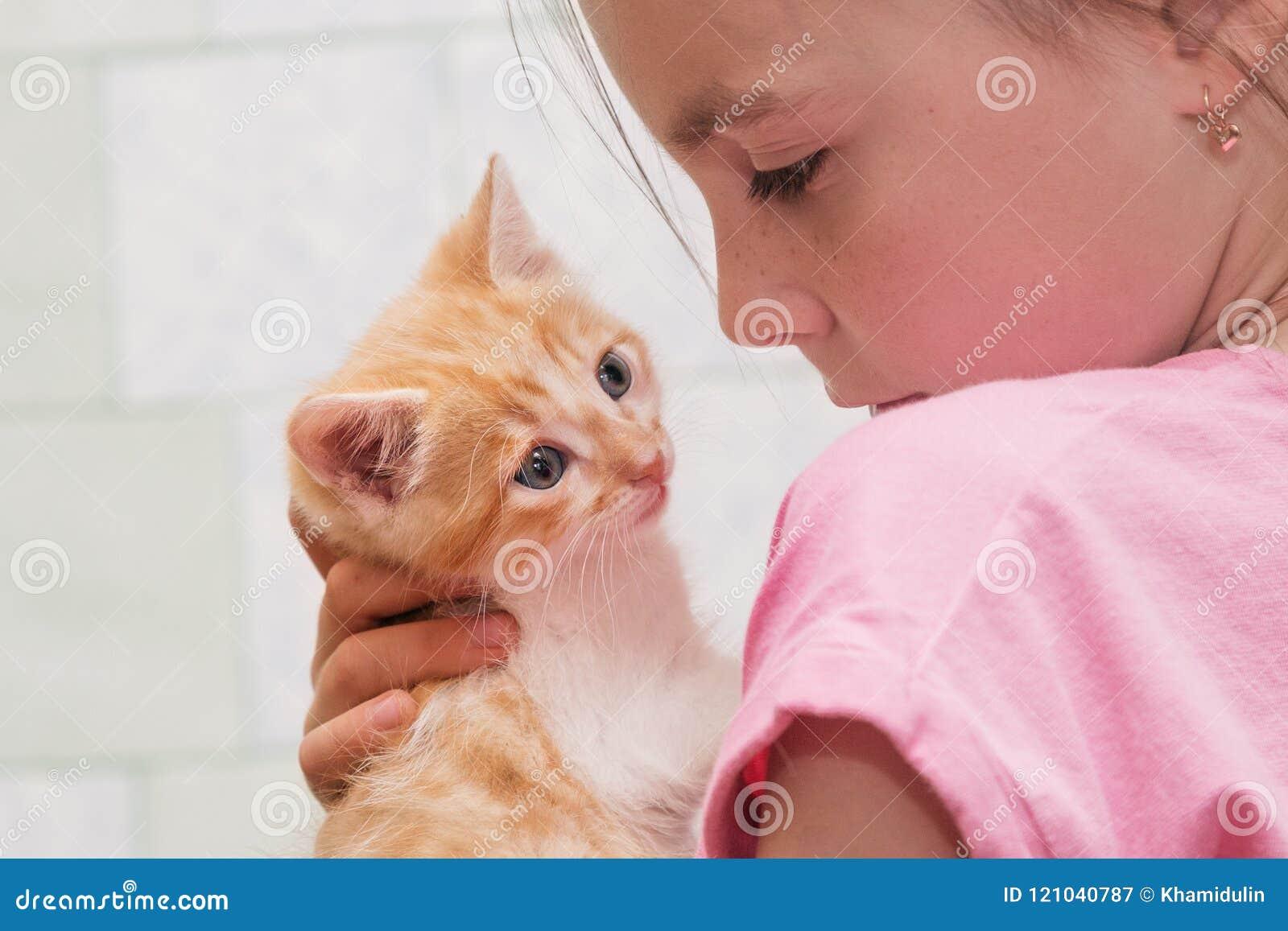 一个小女孩拿着在她的胳膊和拥抱的一只小猫