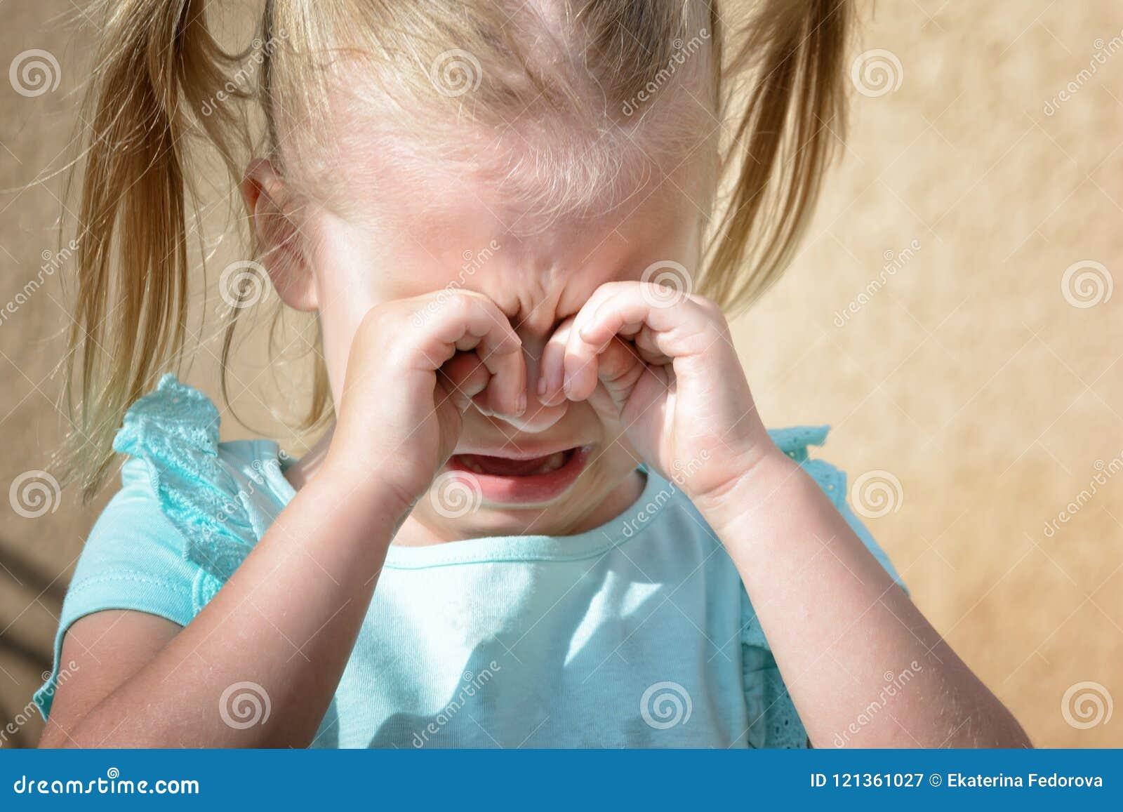 一个小女孩是哭泣和摩擦她的眼睛用她的手 儿童` s歇斯底里