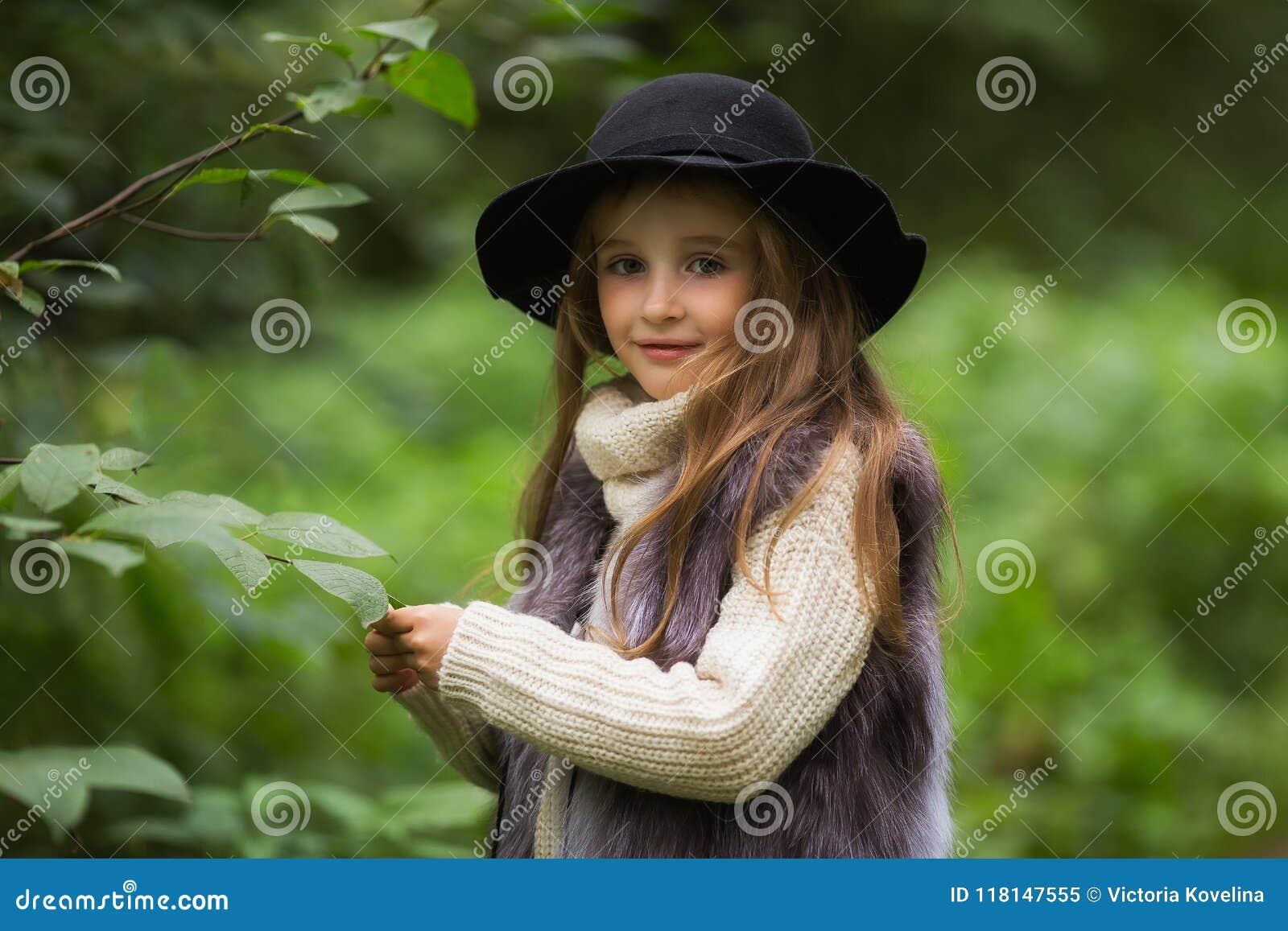 一个小女孩的春天画象 有大棕色眼睛的甜女孩在黑帽会议和毛皮授予