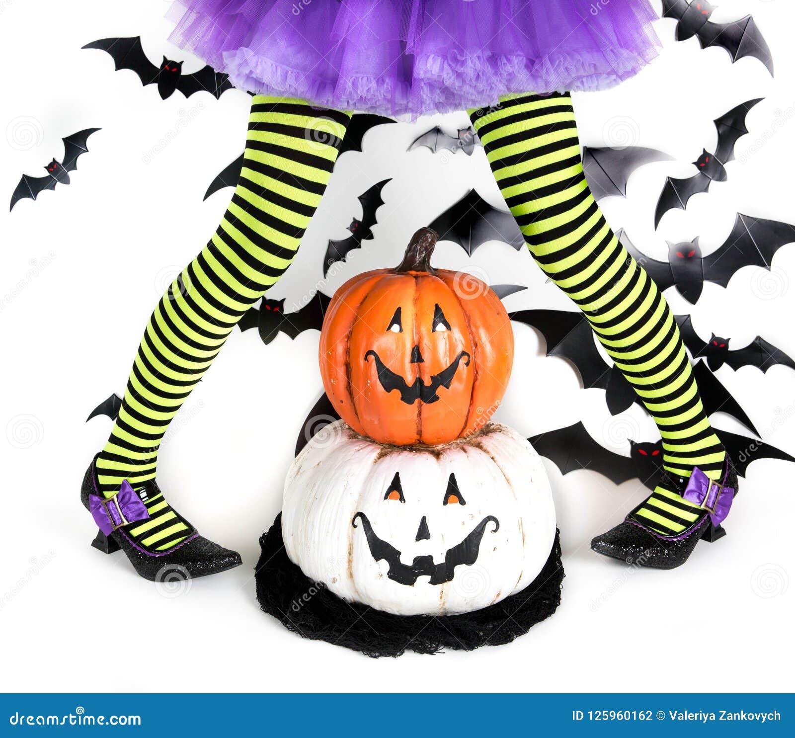 一个小女孩的滑稽的绿色黑镶边腿有一个巫婆的万圣夜服装的有巫婆鞋子和兴高采烈的万圣夜南瓜的