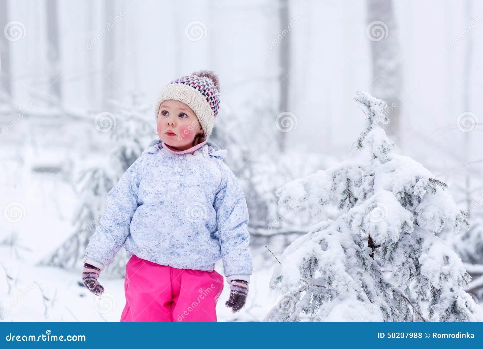 一个小女孩的画象冬天帽子的在雪花背景的雪森林里图片