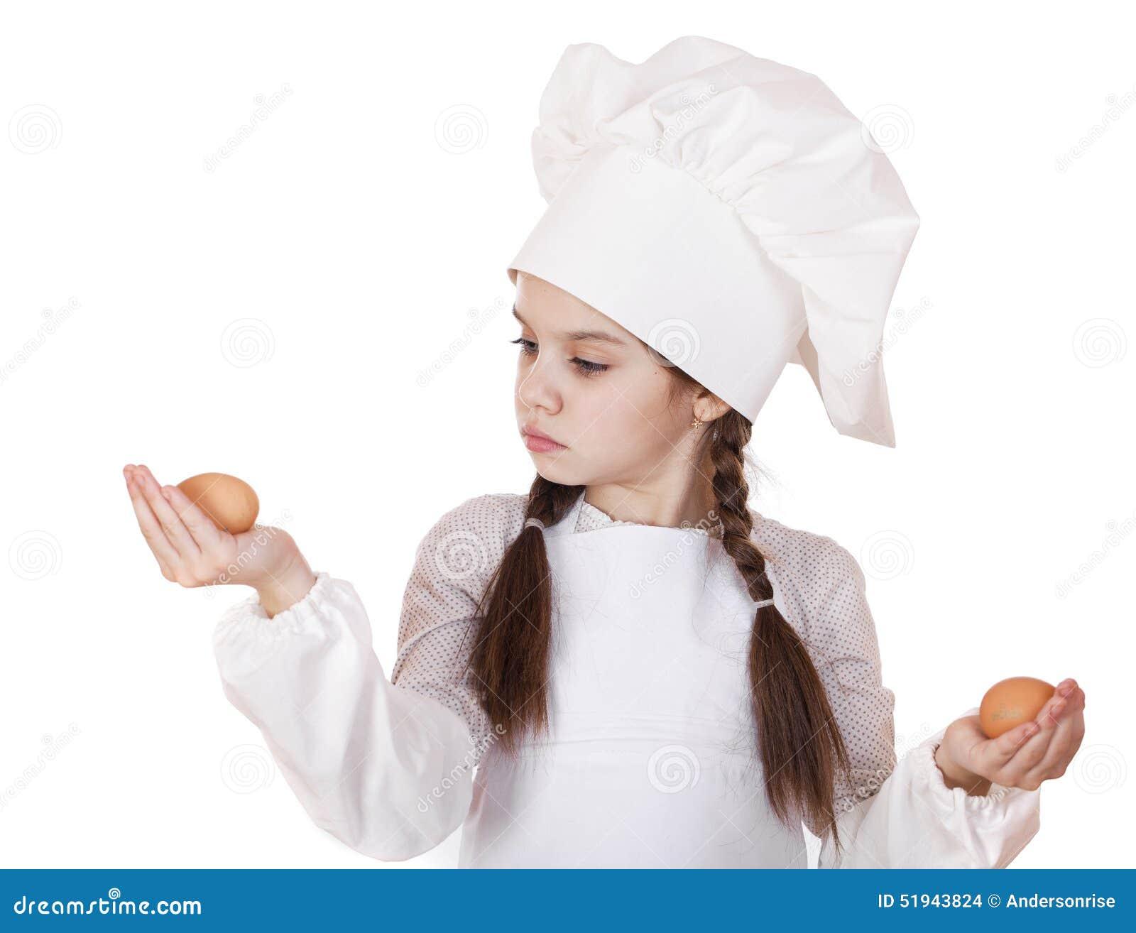一个小女孩的画象拿着两个鸡鸡蛋的一条白色围裙的,隔绝在白色背景.图片