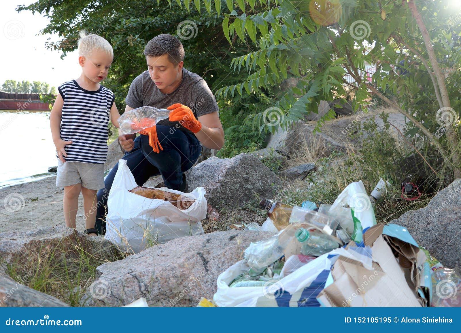 一个小孩子收集在海滩的垃圾 他的爸爸在哪里指向他的手指投掷垃圾 父母教孩子洁净