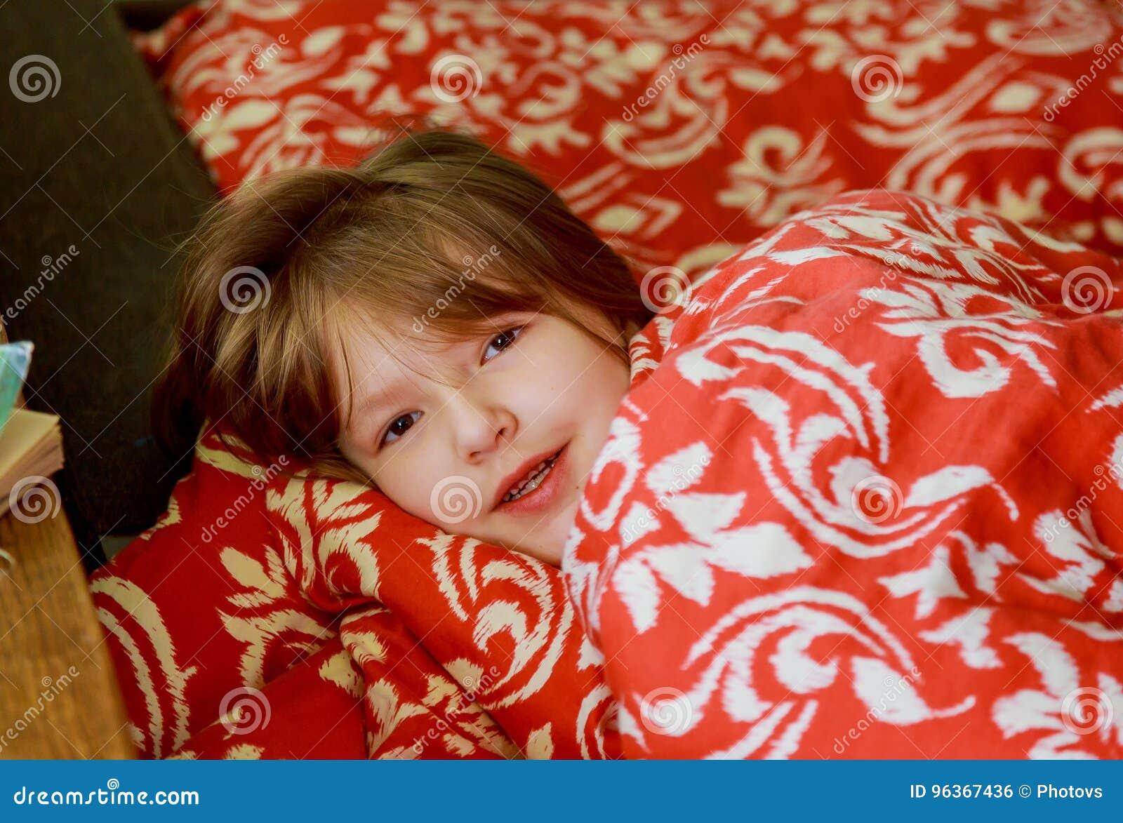 一个小害病的女孩在卧室 小女孩坐床佩带睡衣
