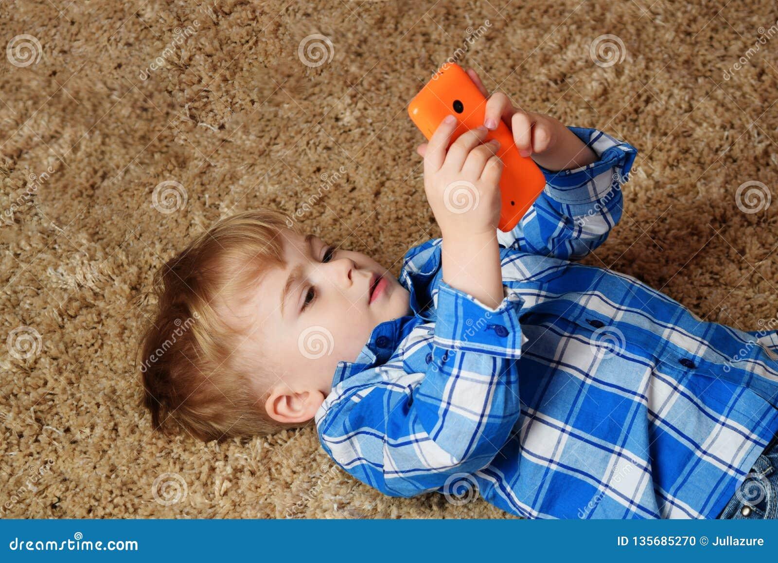 一个小男孩在地毯说谎并且充当电话 使用智能手机的小男孩