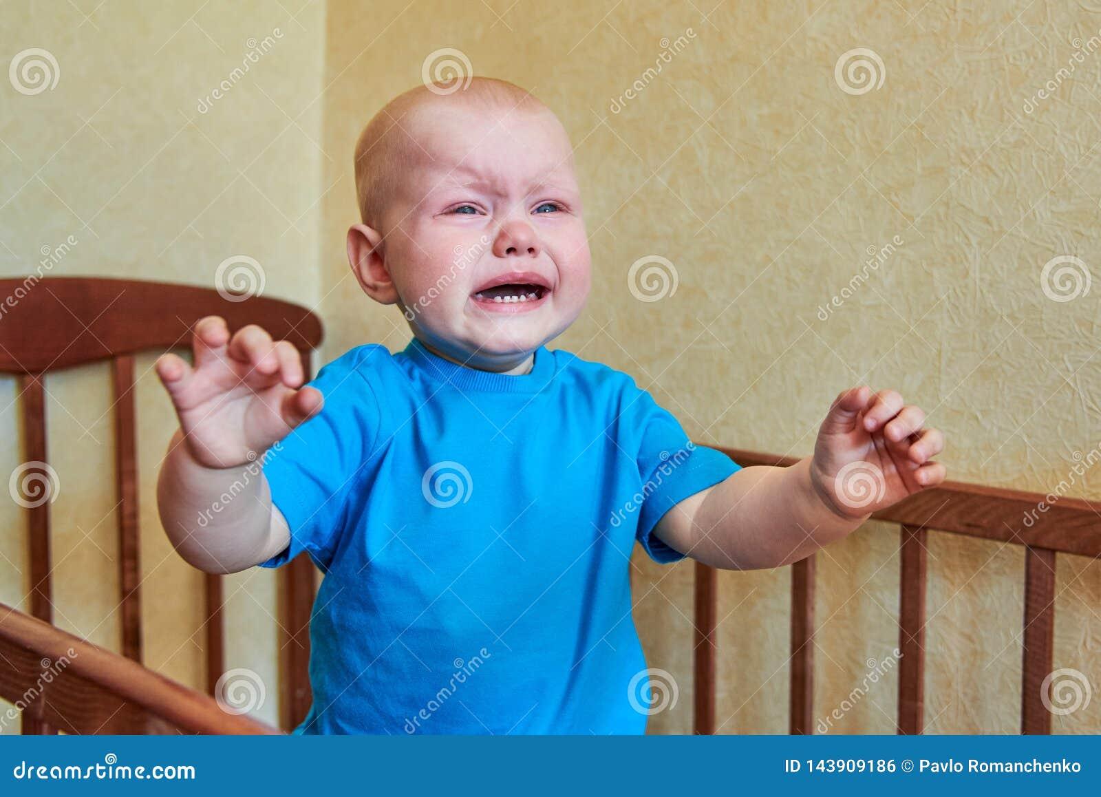一个小男孩在小儿床站立,哭泣并且告诉母亲