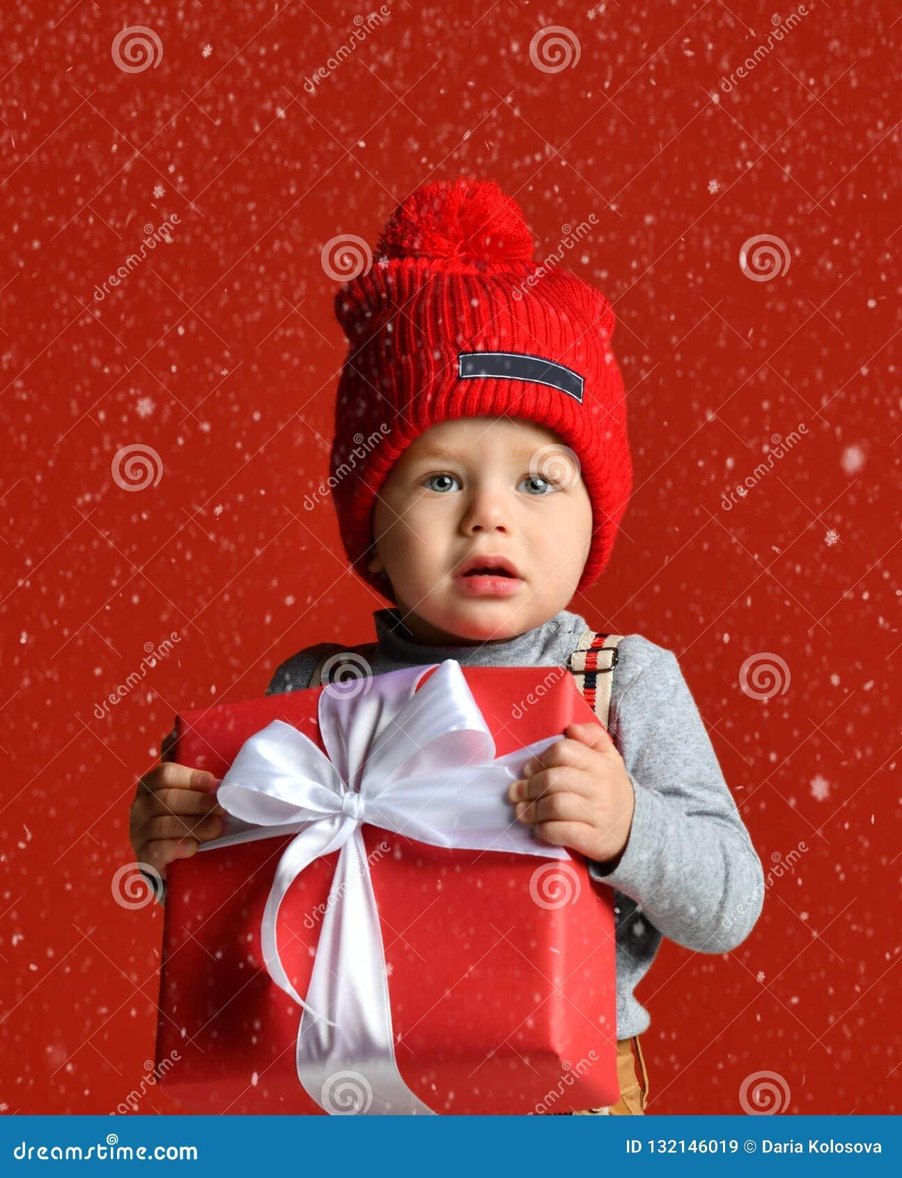 一个小男孩的画象一个红色帽子的有绒球的 拿着有一把白色弓的一个大礼物盒