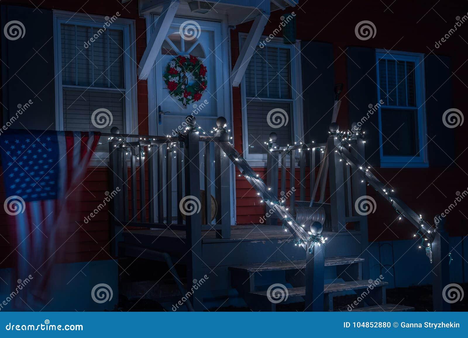 一个小简单的房子的门廊的夜照片用圣诞节诗歌选和花圈装饰的 美国的旗子开发