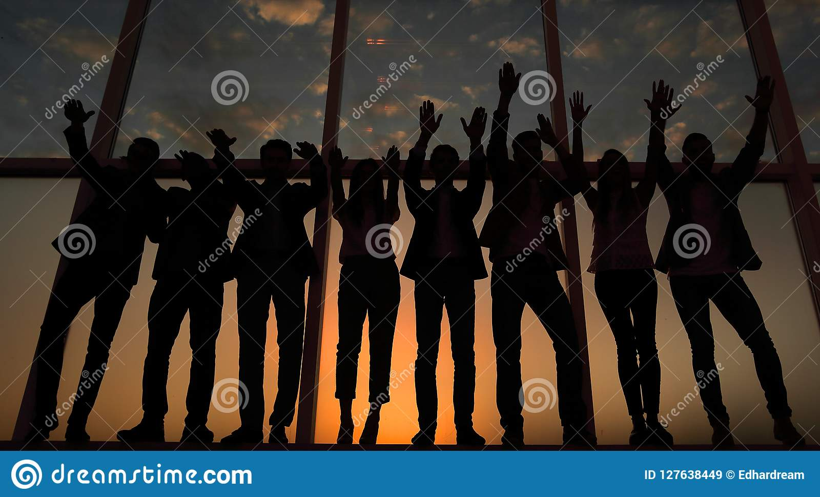 一个小组的剪影举他们的手的商人