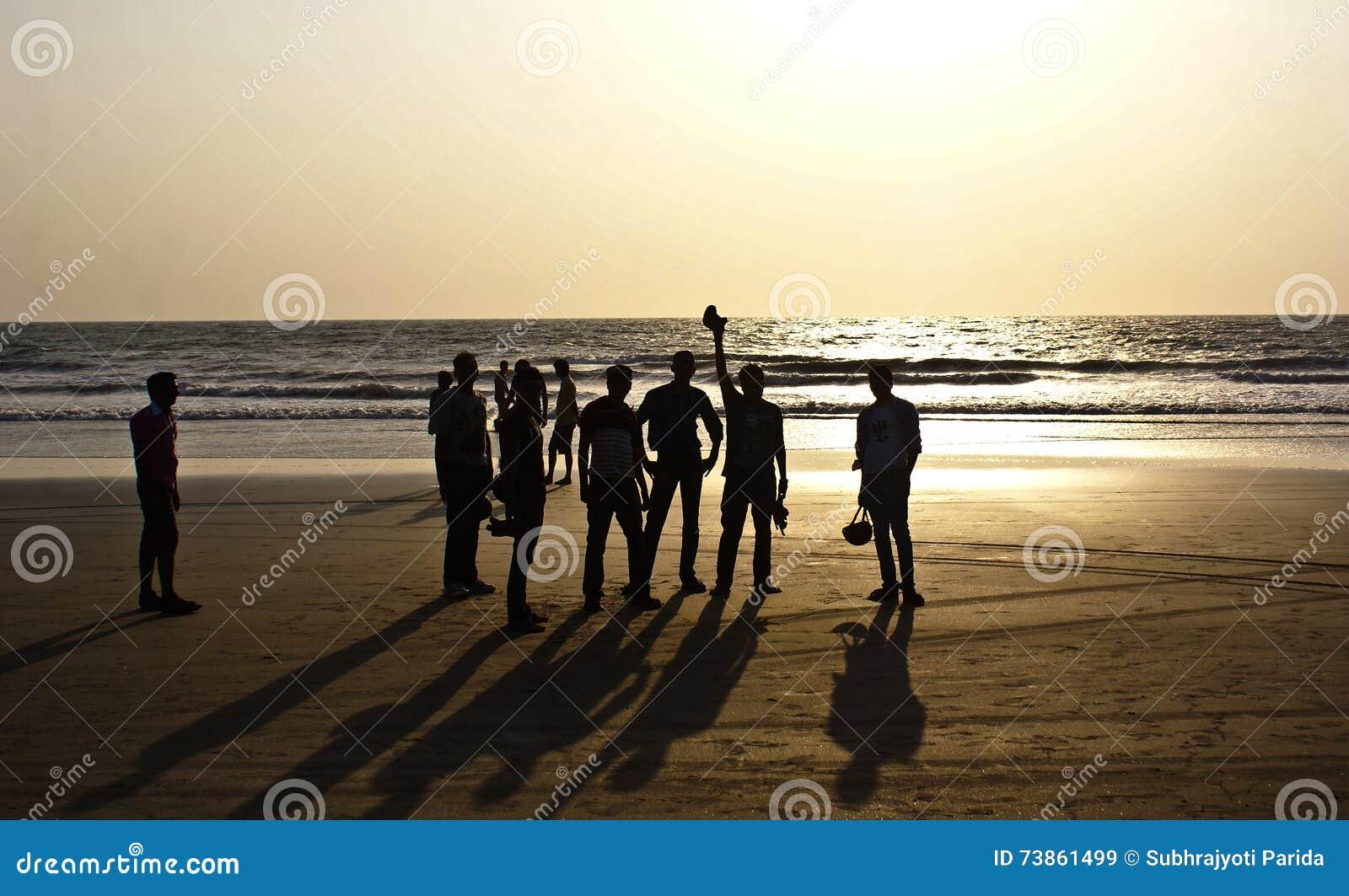 一个小组朋友现出轮廓在Arambol海滩,北部果阿