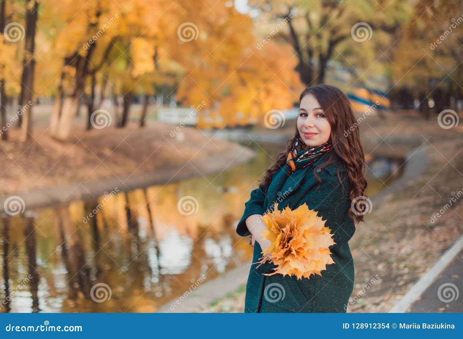 一个少妇在秋天公园走 她支持湖 穿一件绿色外套的深色的妇女