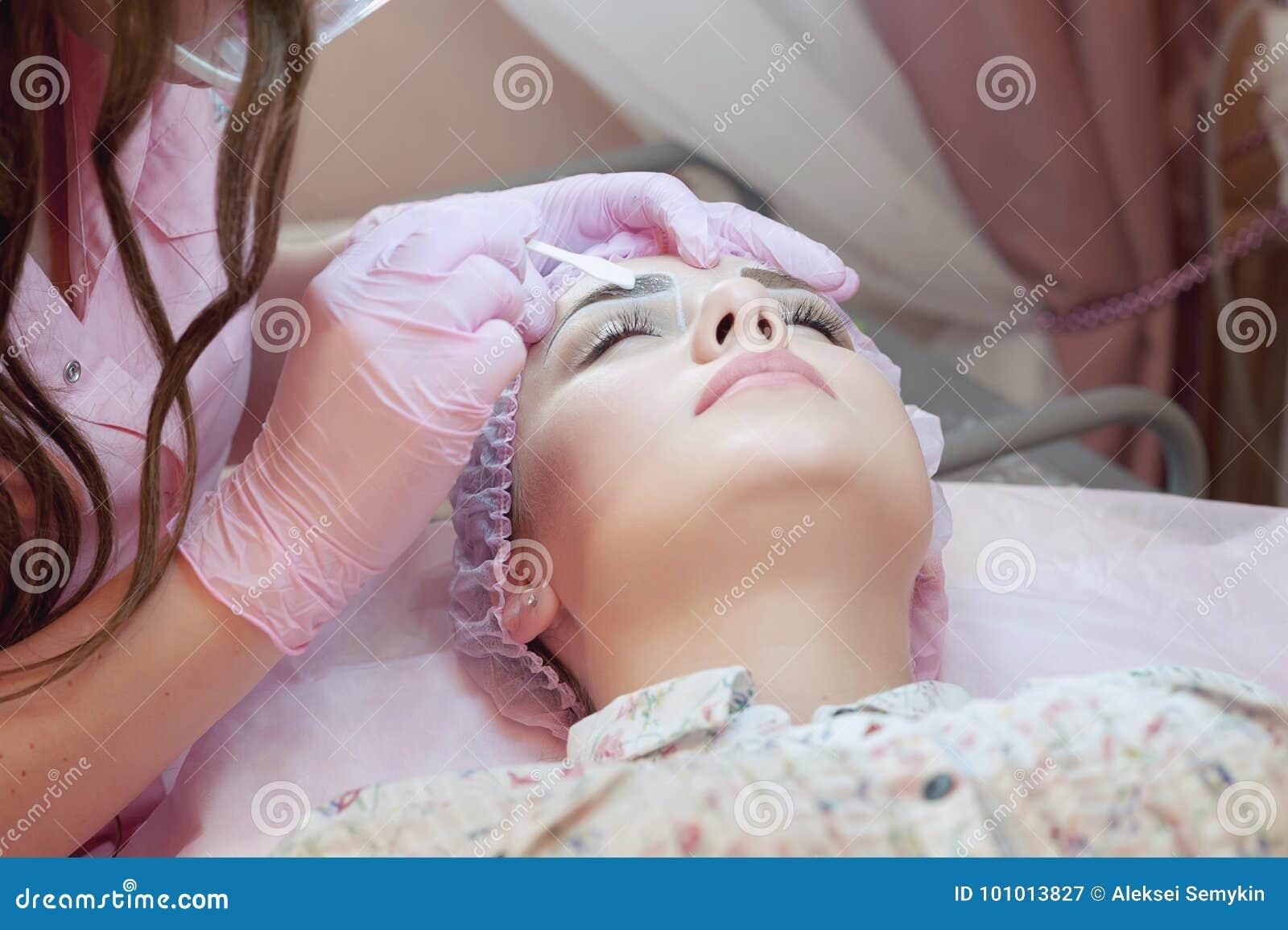 一个少妇说谎并且得到她的在美容院的眼眉构成  使用在眼眉的永久构成 大师w