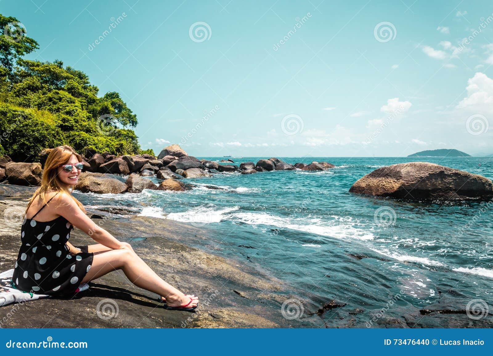 一个岩石海滩的女孩在美丽的海岛(Ilhabela),巴西