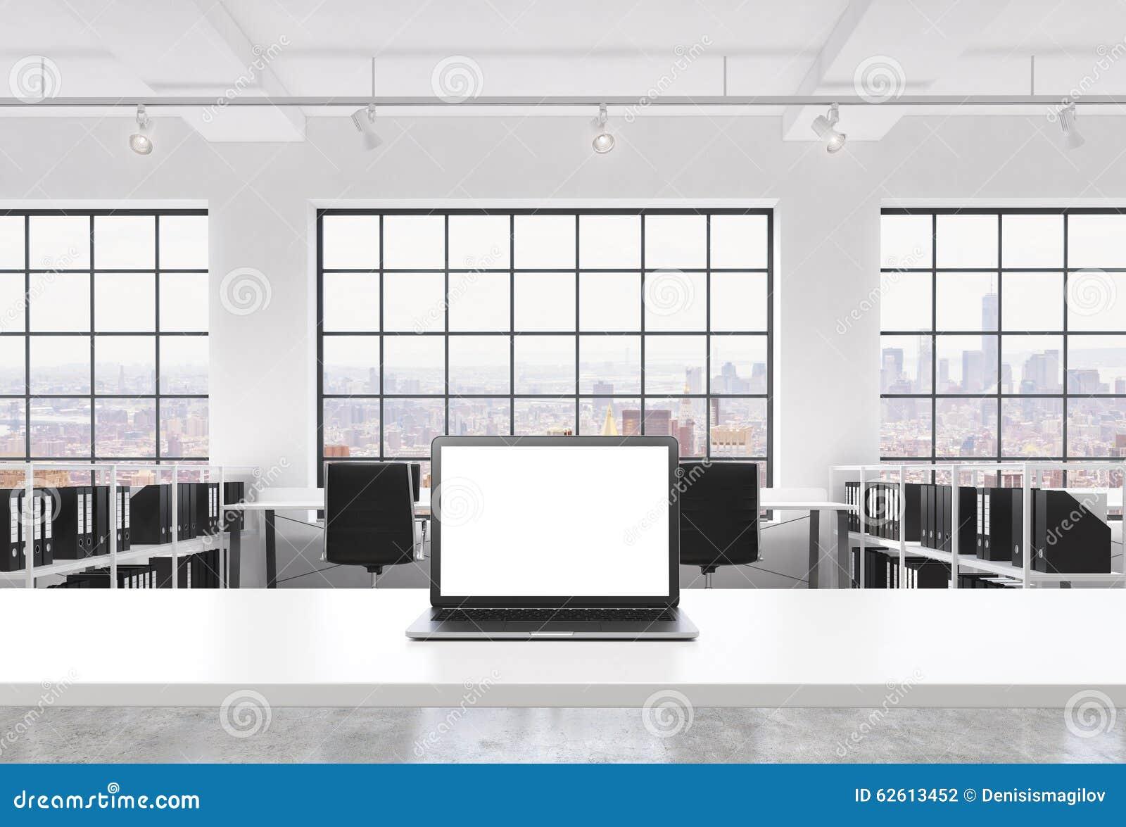 一个工作场所在一个明亮的现代顶楼露天场所办公室 一张运转的书桌装备有白色拷贝空间的一台现代膝上型计算机在Th