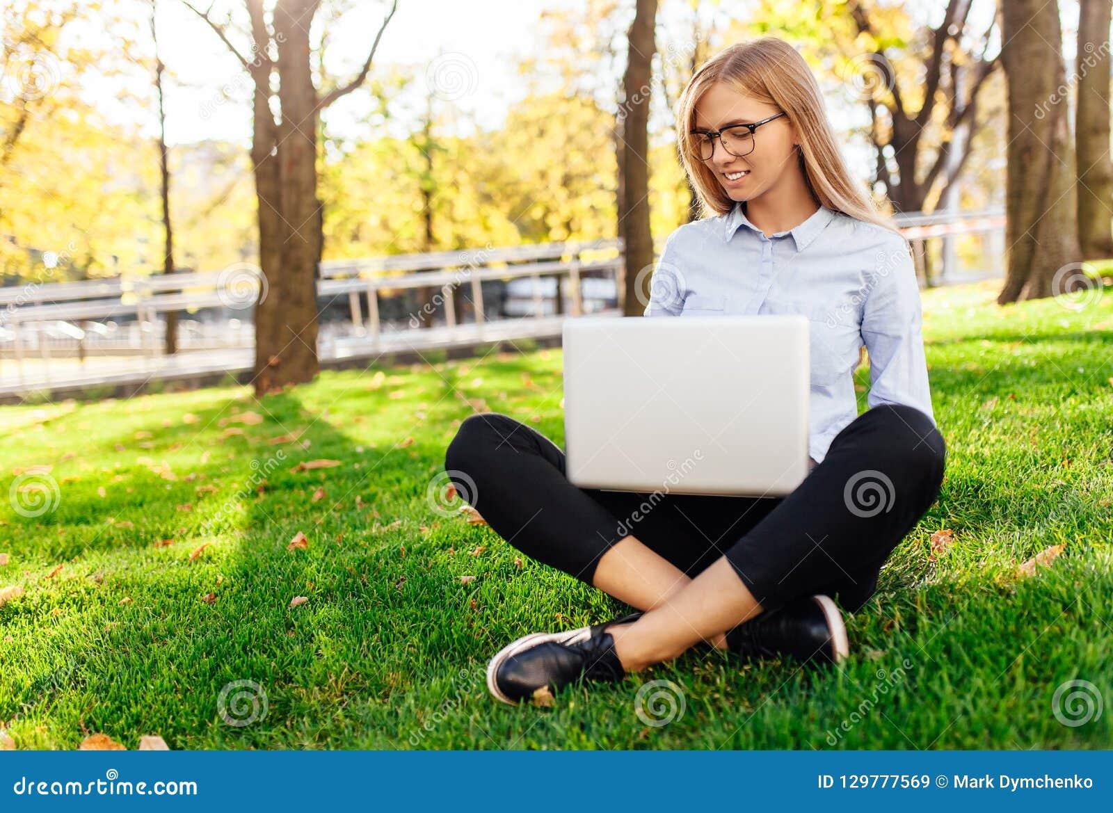 一个年轻惊人的夫人的图象,坐在公园,使用手提电脑,坐绿色草坪