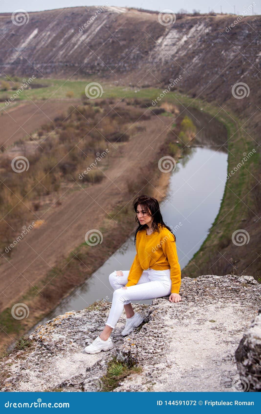 一个年轻旅客女孩坐谷上面  少女爱狂放的生活,旅行,自由
