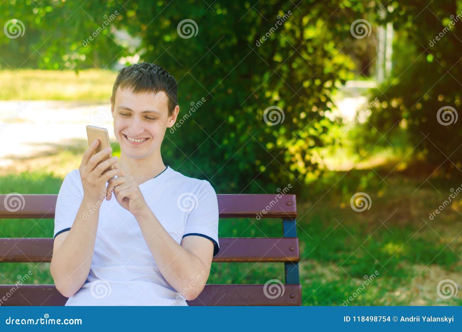 一个年轻欧洲人坐一条长凳在城市公园并且把手指指向电话 一个人微笑着看电话 布加勒斯特c e办公室