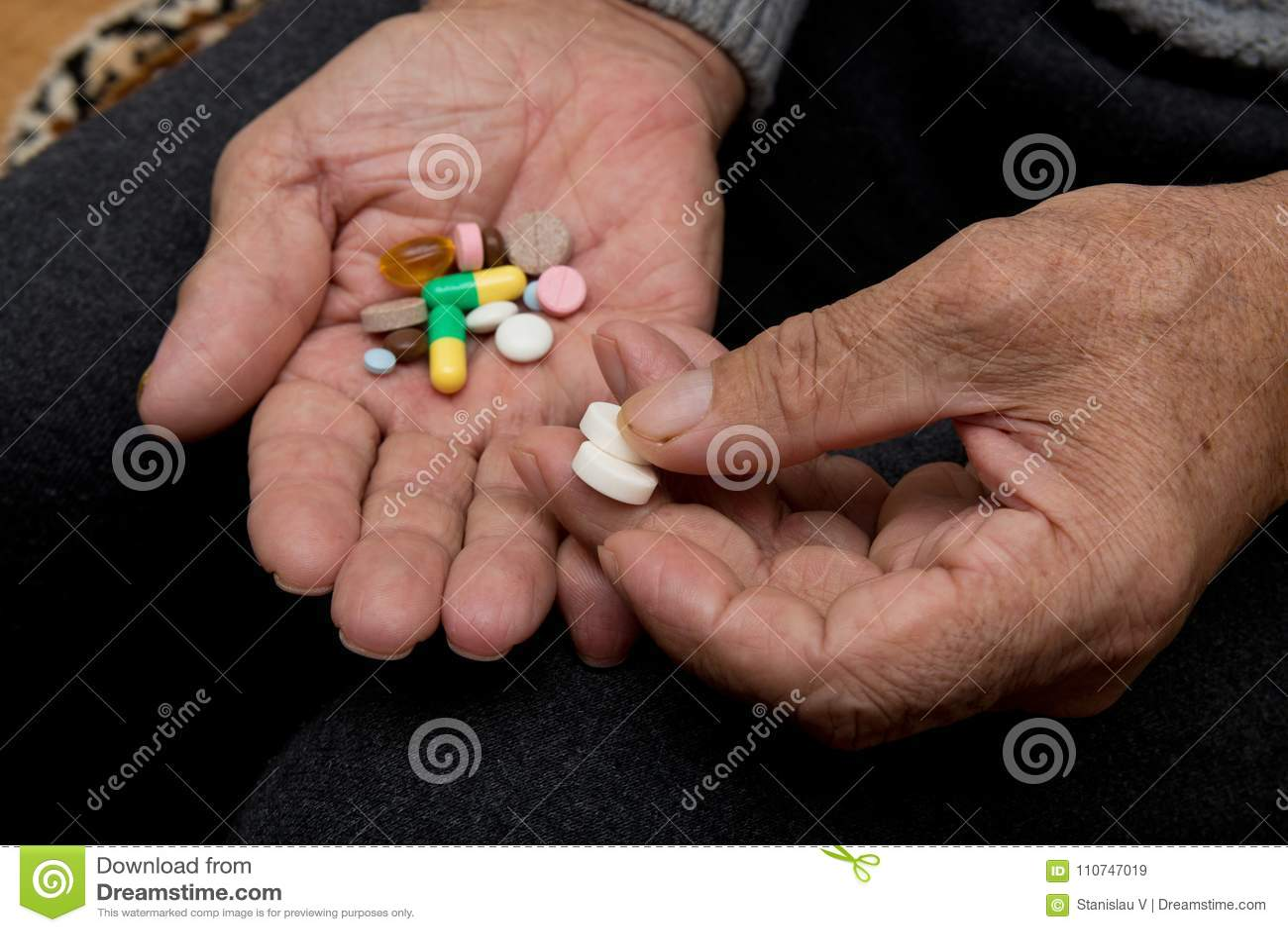 一个年长人在老手上拿着很多色的药片 痛苦的晚年 老人医疗保健