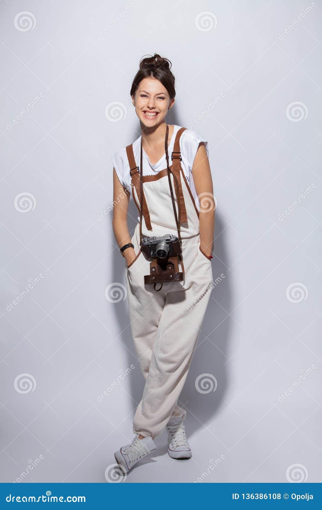 一个微笑的偶然妇女身分和看照相机的全长画象在白色背景的