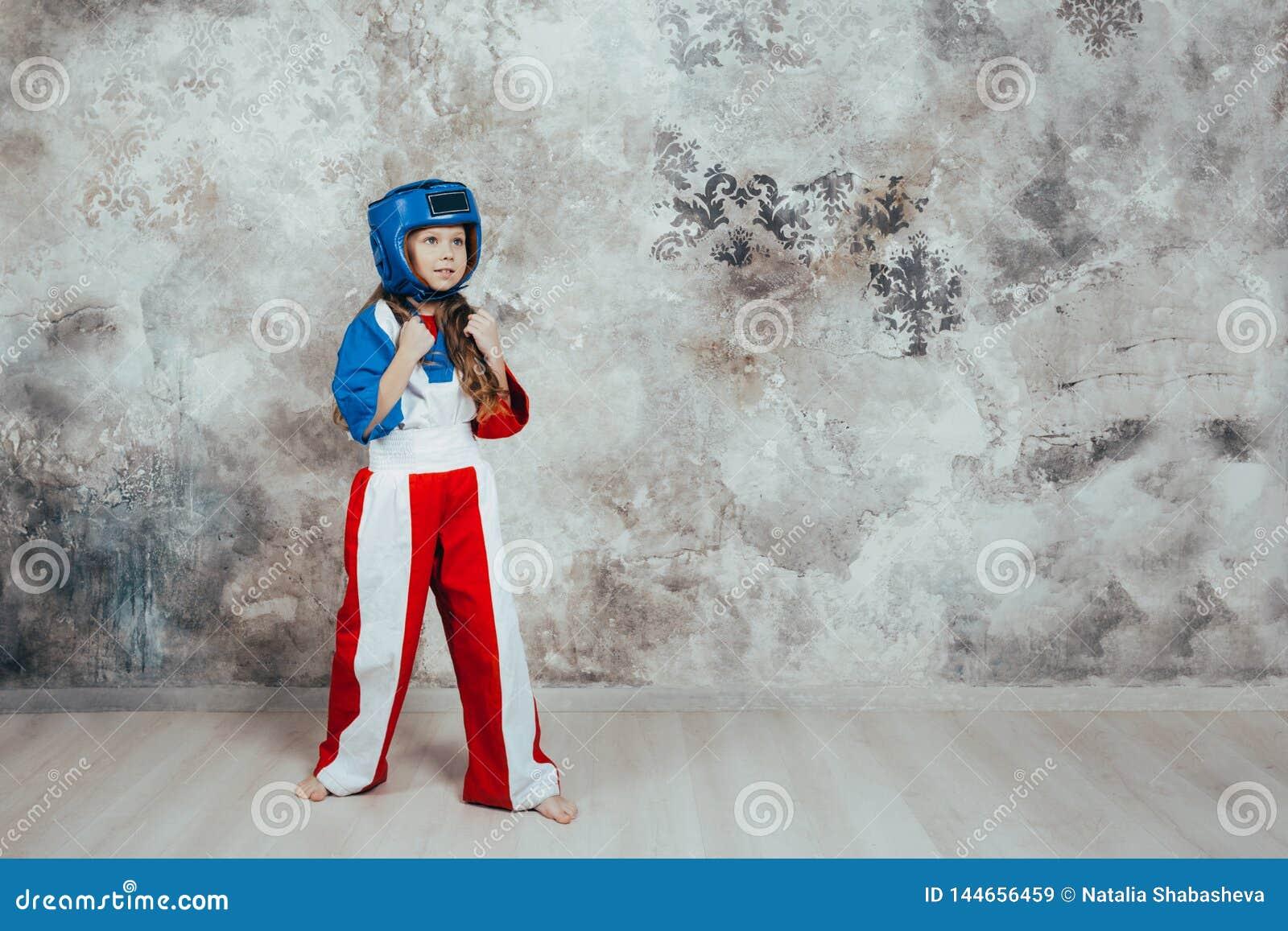 一个微笑的年轻女性跆拳道女孩的画象对难看的东西墙壁
