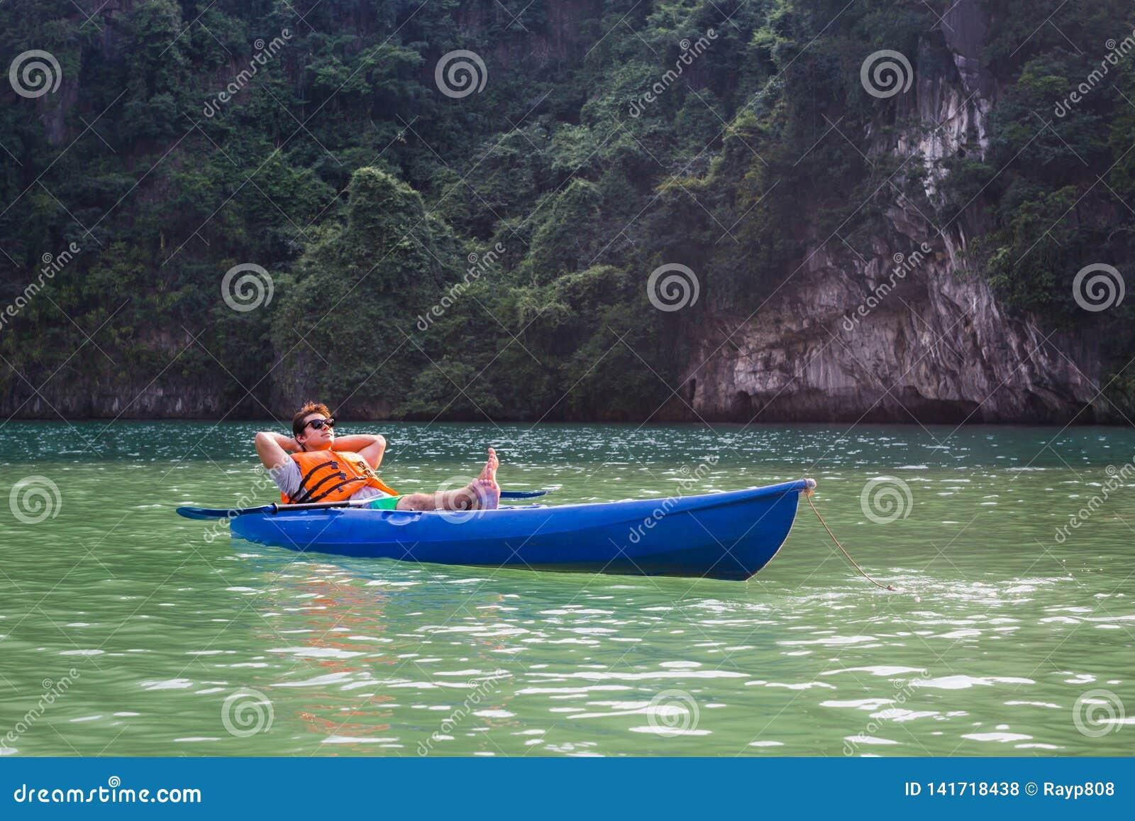 一个愉快的人在皮船小船坐湖放松