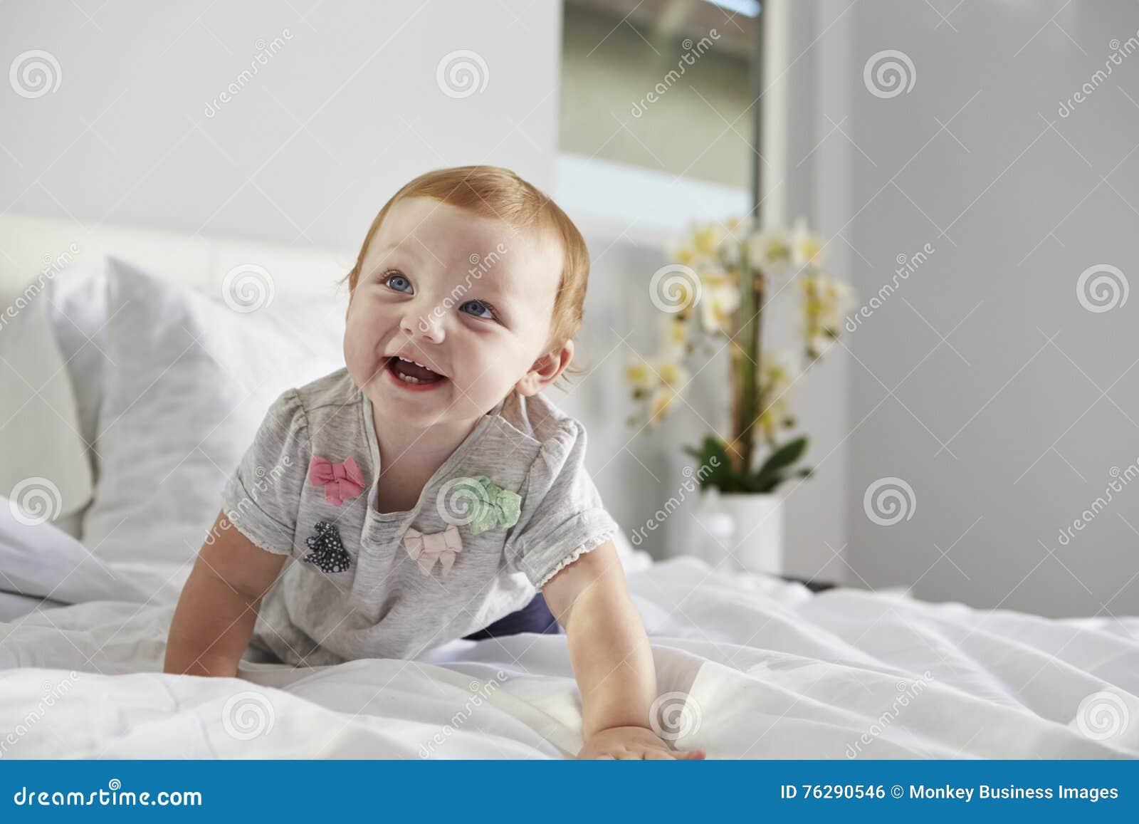 一个愉快的女婴爬行在床上的,在右边的拷贝空间