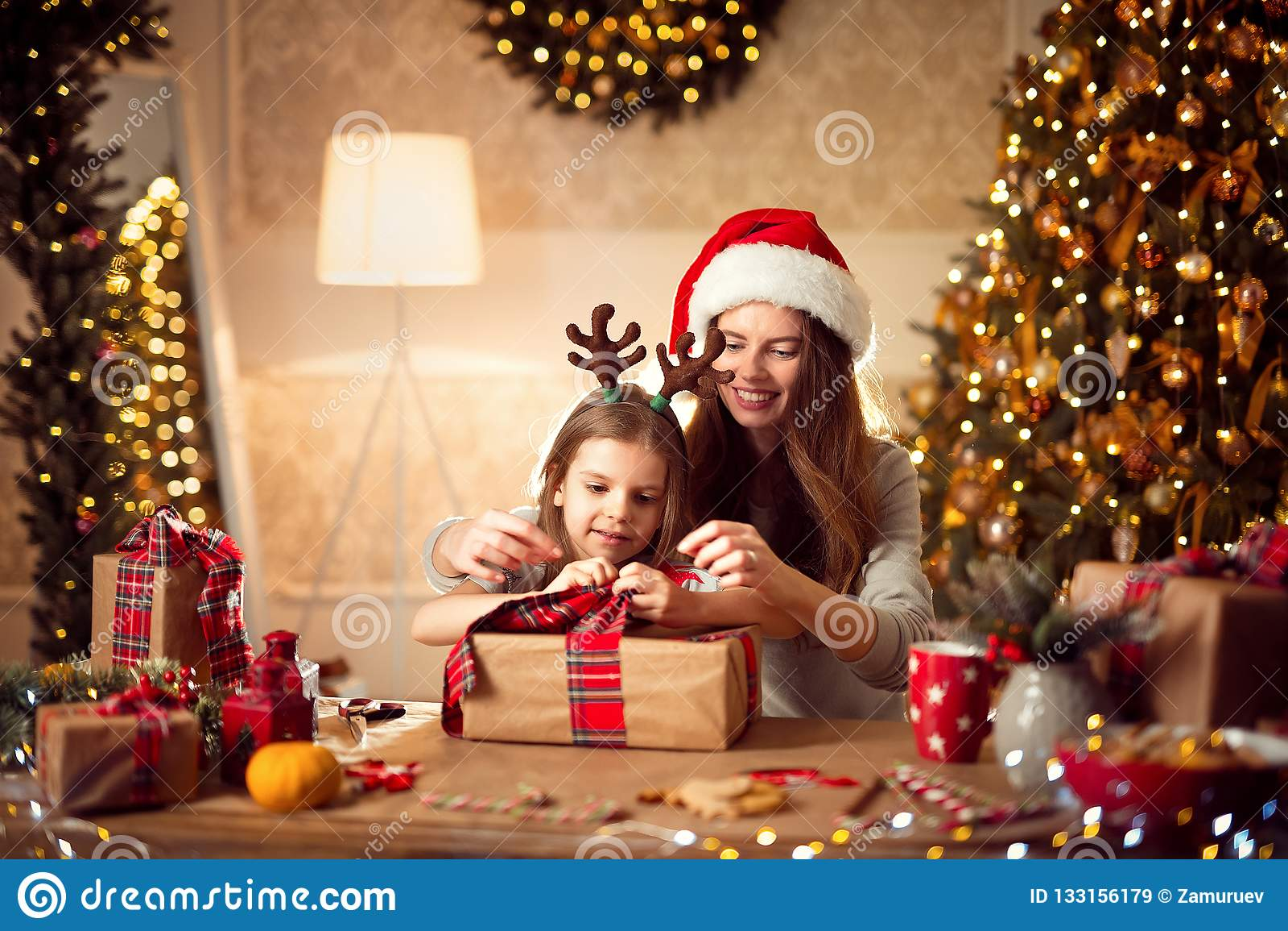 一个愉快的家庭母亲和孩子包装圣诞节礼物