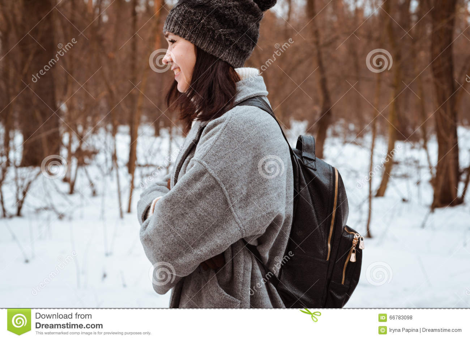 一个愉快的美丽的女孩的画象有棕色头发的在冬天森林在行家样式,生活方式穿戴了