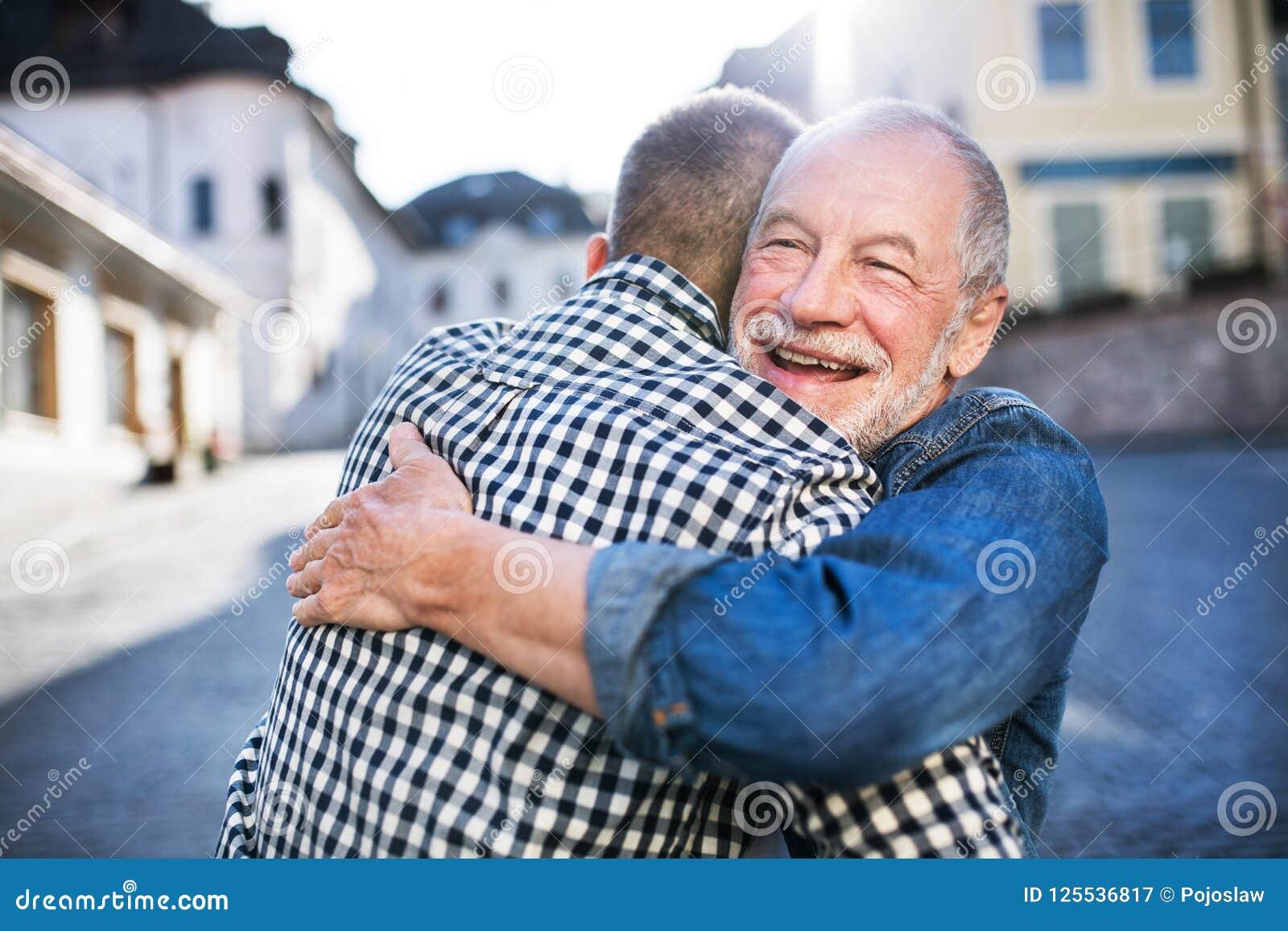 一个成人行家儿子和他的资深父亲在镇里,拥抱