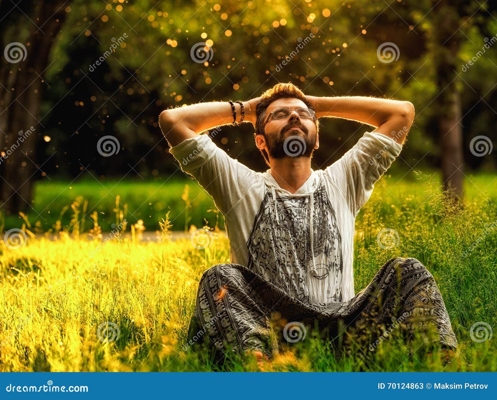 一个有胡子的人是松弛在绿草在公园