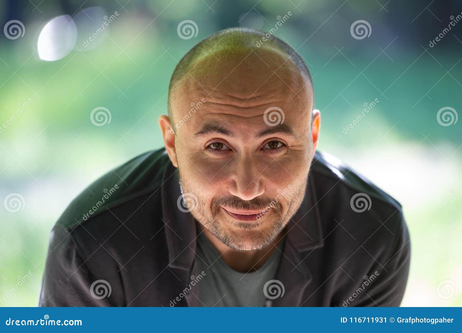 一个有胡子的微笑的秃头人的面孔在公园