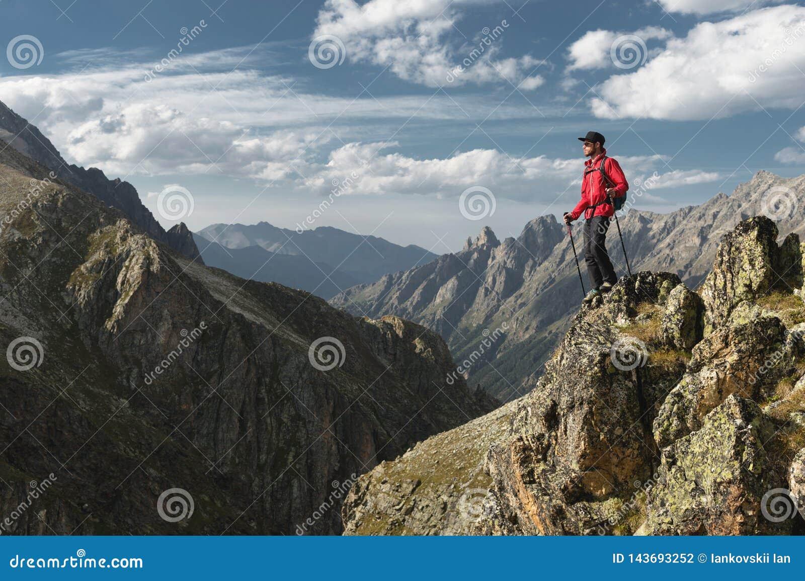 一个有胡子的旅客行家有背包的和在高峭壁的迁徙的杆立场的搬运工太阳镜和一个盖帽的