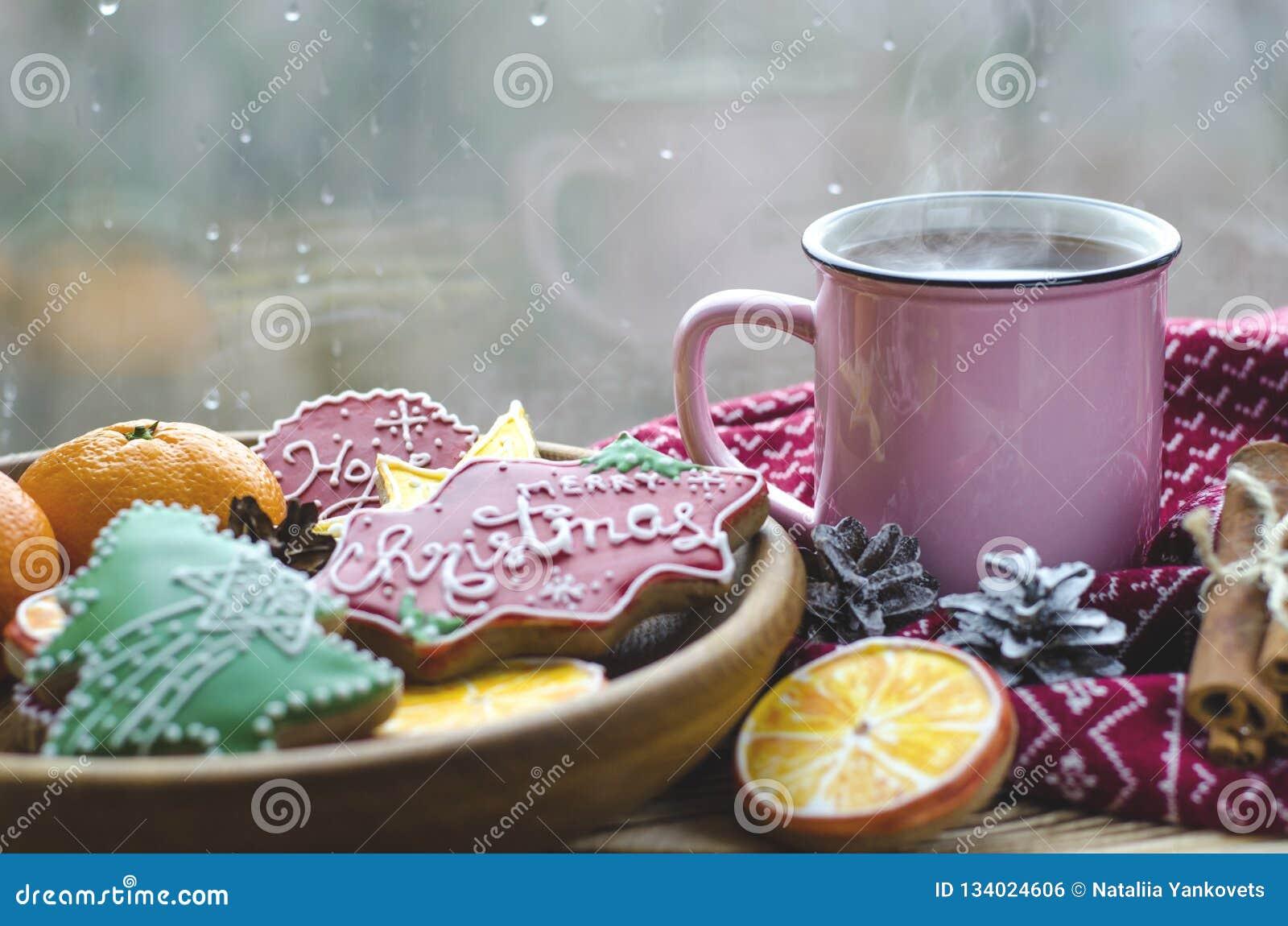 一个杯子在一张木桌上的热的茶立场在桔子做的姜饼曲奇饼的一块木板材旁边