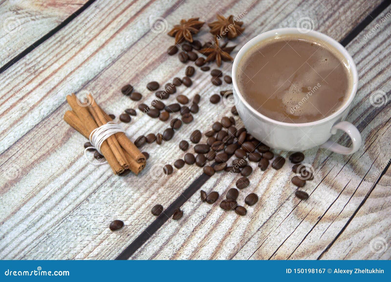 一个杯子在桌上的热奶咖啡,在咖啡豆、八角和一束桂香附近 r