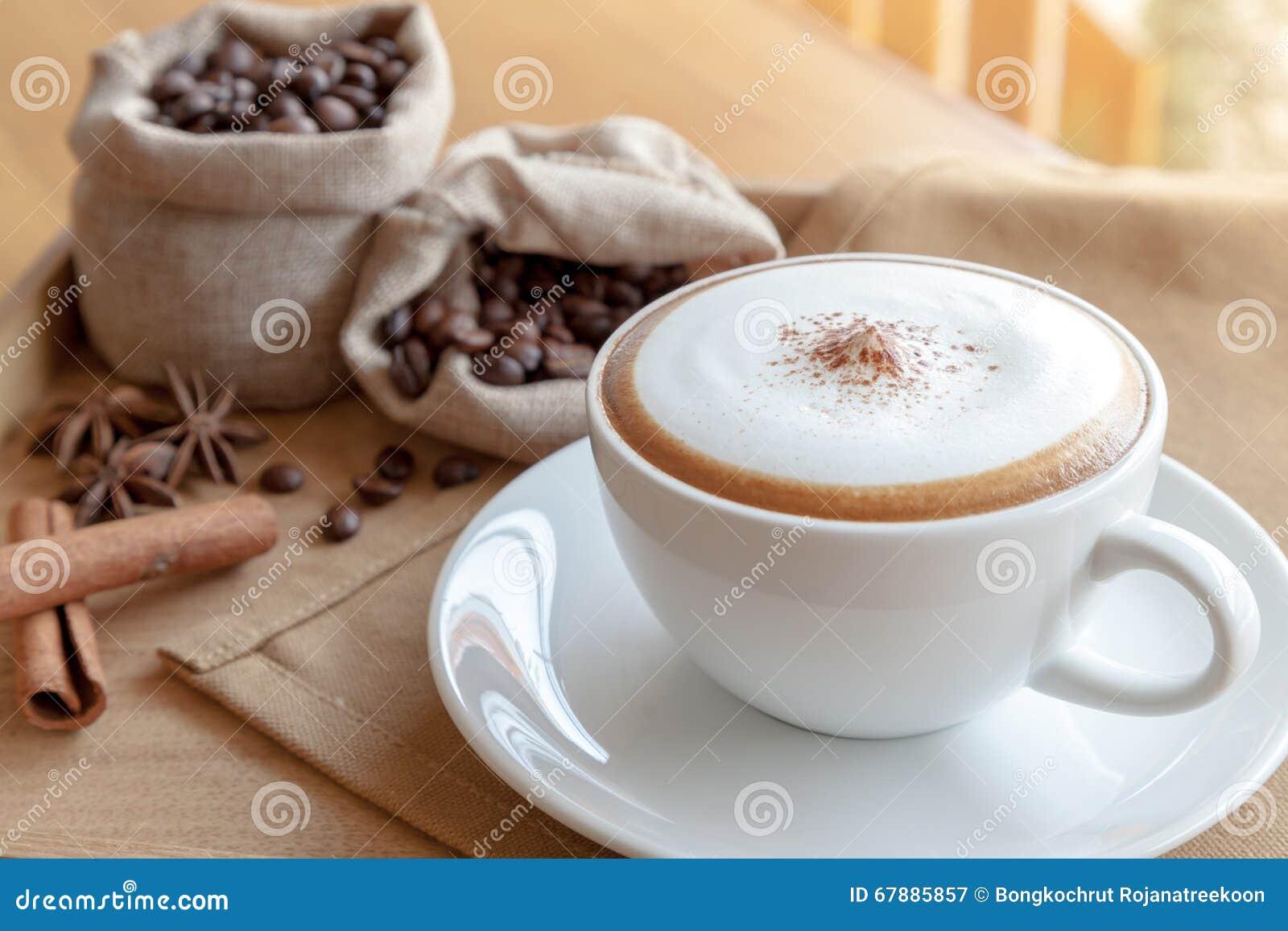 一个杯子热奶咖啡和草本在餐巾