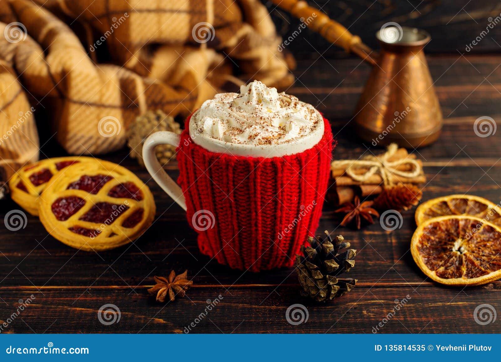 一个杯子热的咖啡,在一个被编织的盖子和自创曲奇饼,Cezve和香料,在一张木桌上说谎在方格的格子花呢披肩附近