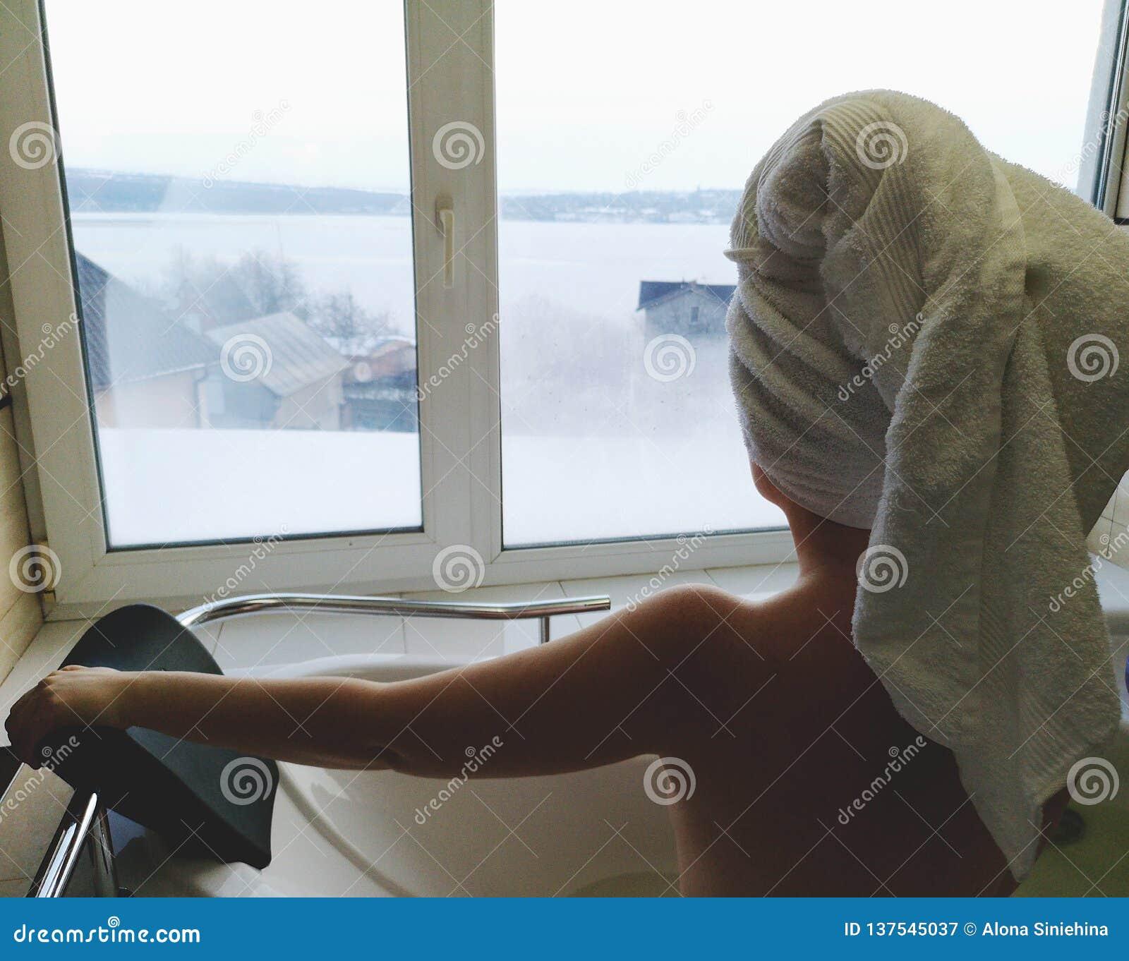 一个浴盆的美女 极可意浴缸在旅馆里,从窗口的全景在卫生间里