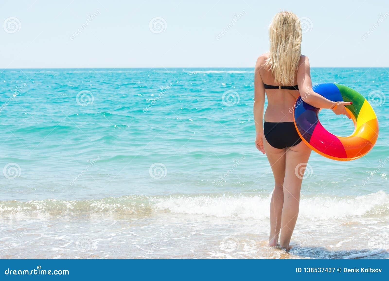 一个海滩假日 比基尼泳装的美丽的性感的妇女有可膨胀的圈子的看到海