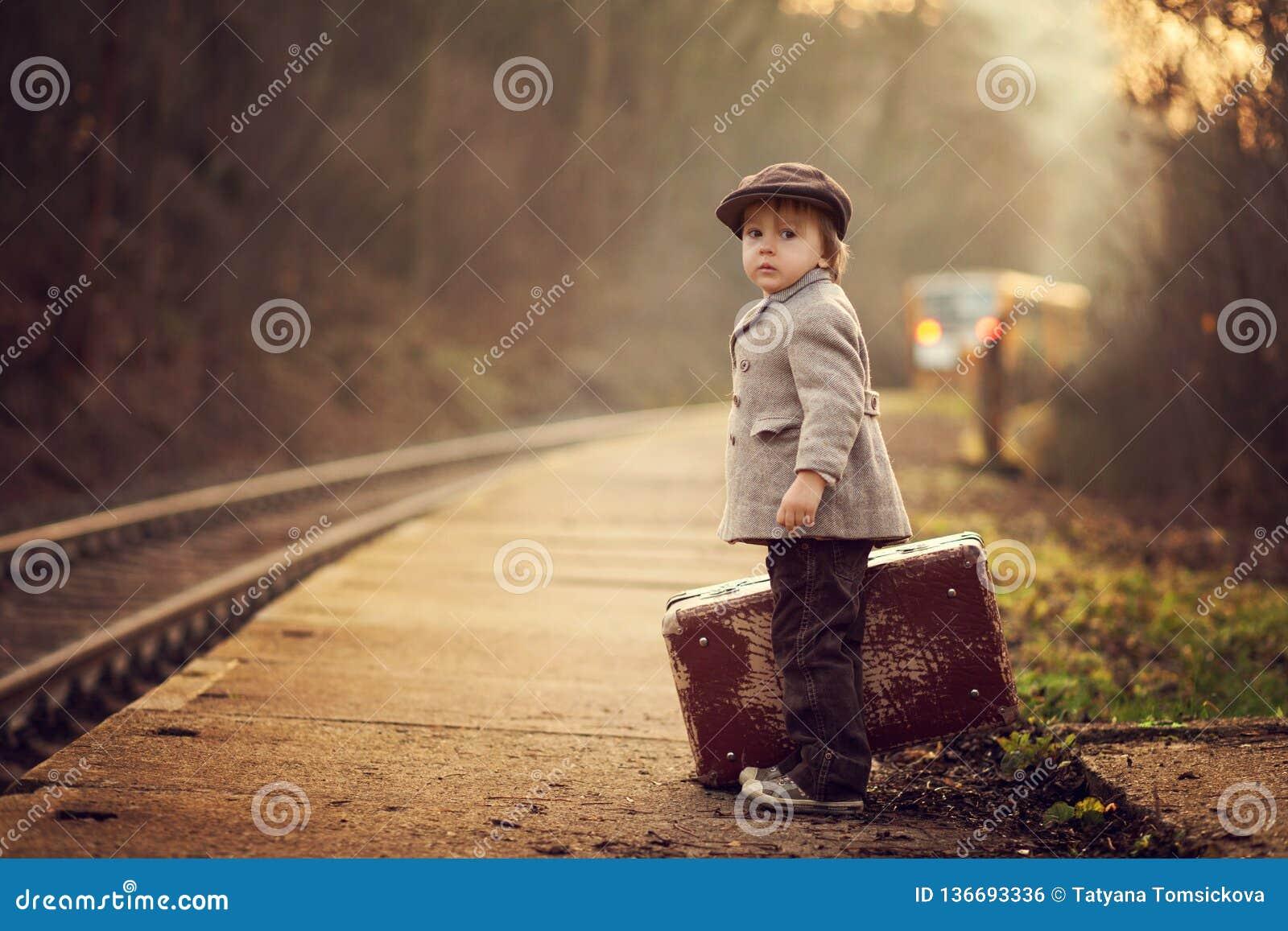一个火车站的可爱的男孩,等待有手提箱和玩具熊的火车