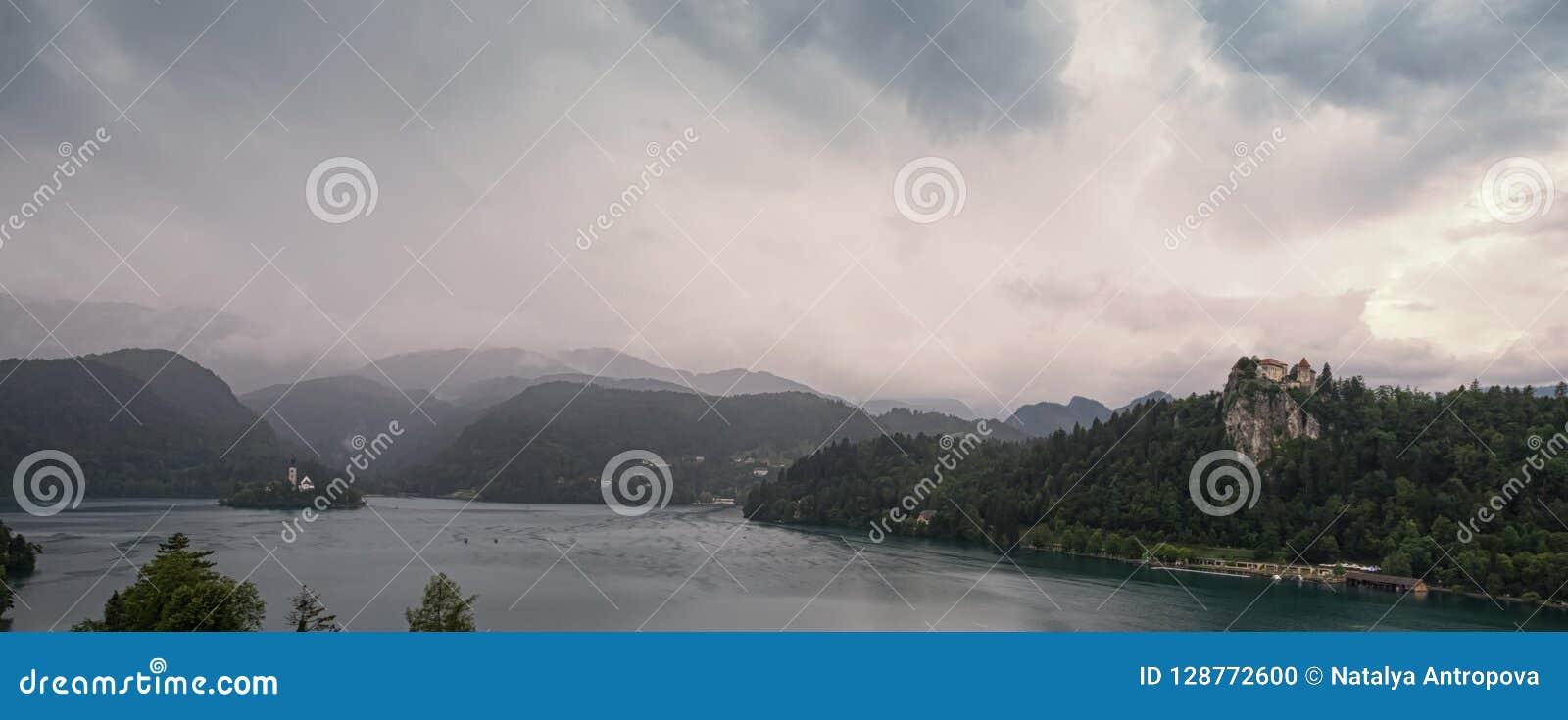 一个灰色和可怕的早晨的全景在高山山的在布莱德湖