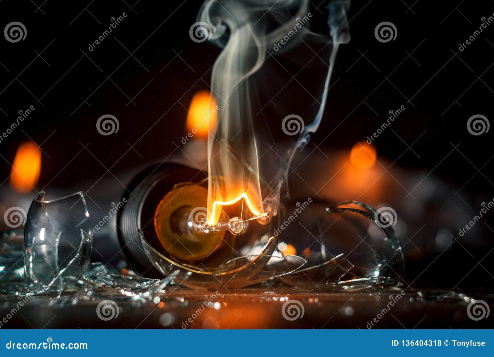 一个灼烧的电灯泡的令人惊讶的爆炸与裂片和烟的