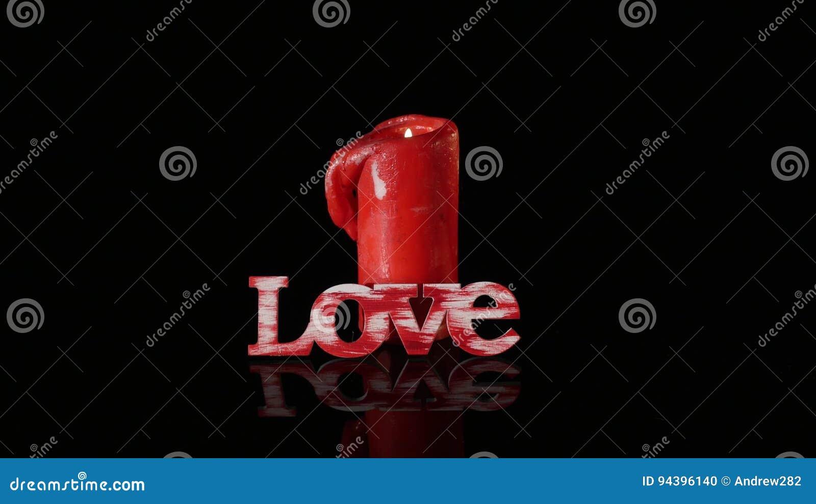 一个灼烧的红色蜡烛在黑背景前面转动
