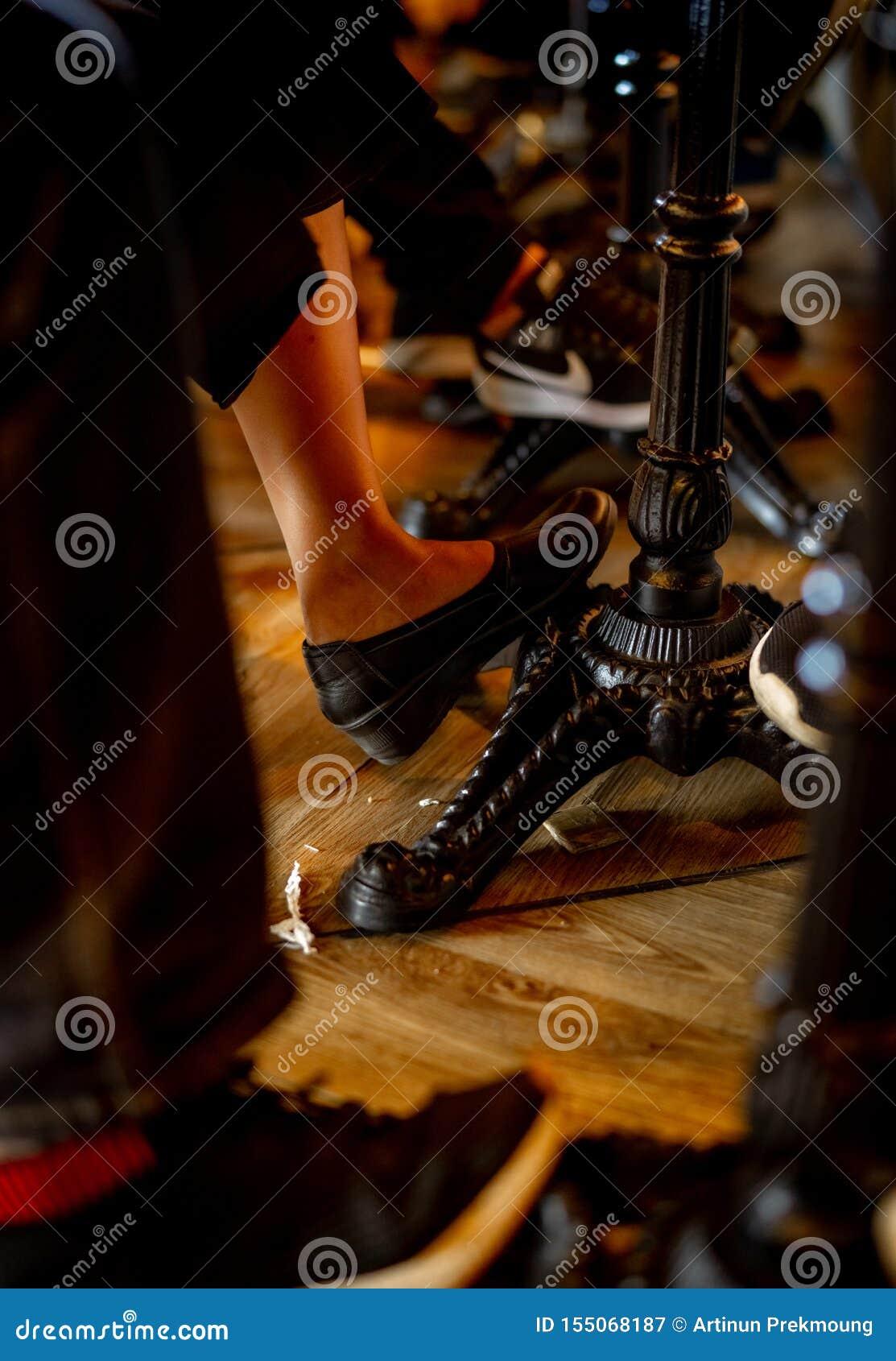 一个男人和一名妇女的特写镜头腿在桌下在咖啡馆 葡萄酒样式桌在餐馆 人们变冷