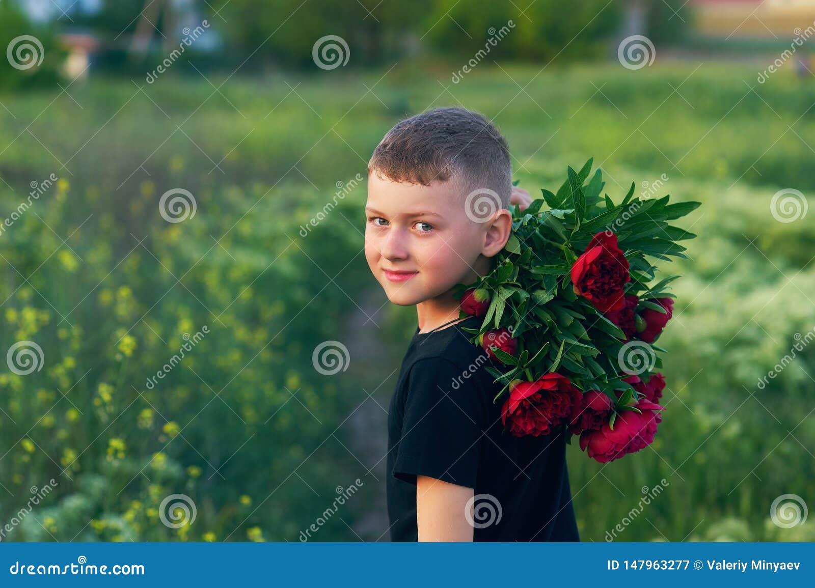 一个男孩的室外画象步行的与牡丹花