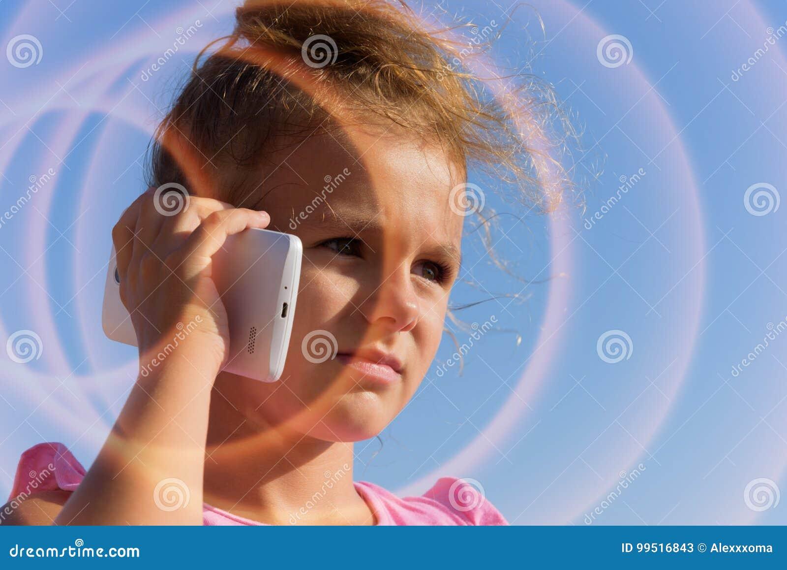 一个相当小女孩由智能手机讲话,斜眼看在蓝天背景的阳光下 Smartphon是奔跑波浪日落2