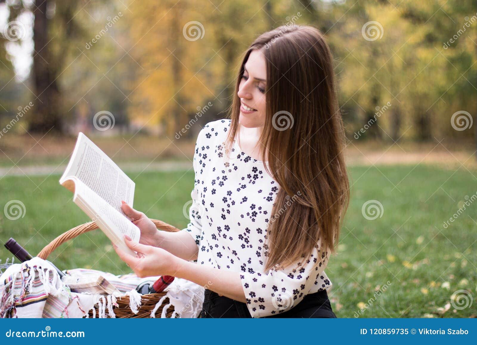 一个相当少妇有野餐在公园,读书