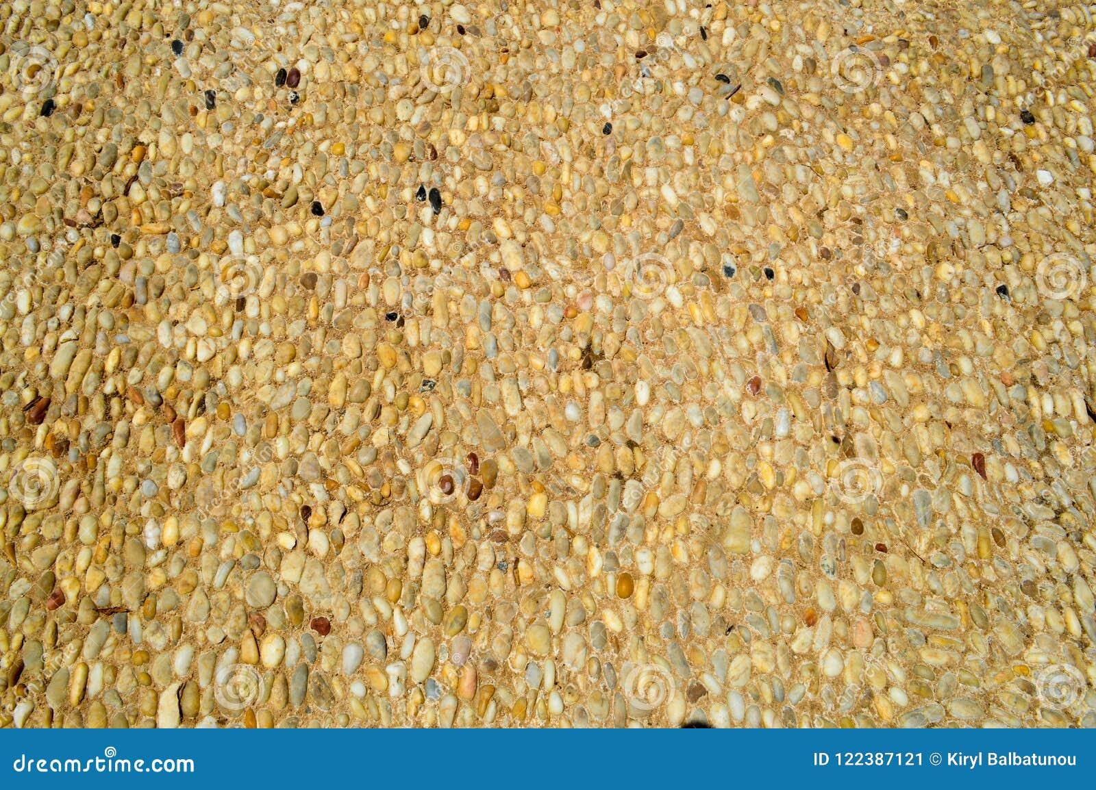 一个石墙、路从小在周围和卵形石头的纹理与沙子与自然老黄色黑褐色缝  背景